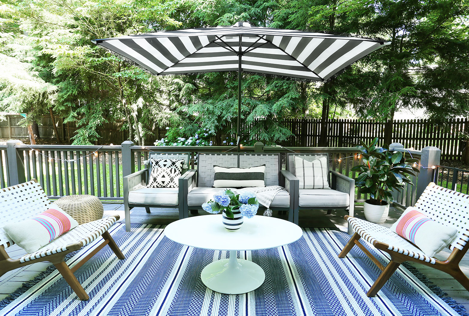 white strap chairs   /   umbrella   /   rug   /   woven pouf   /   coffee table   /   striped vase   /   geo pillow   /   striped pillow   /   cafe lights