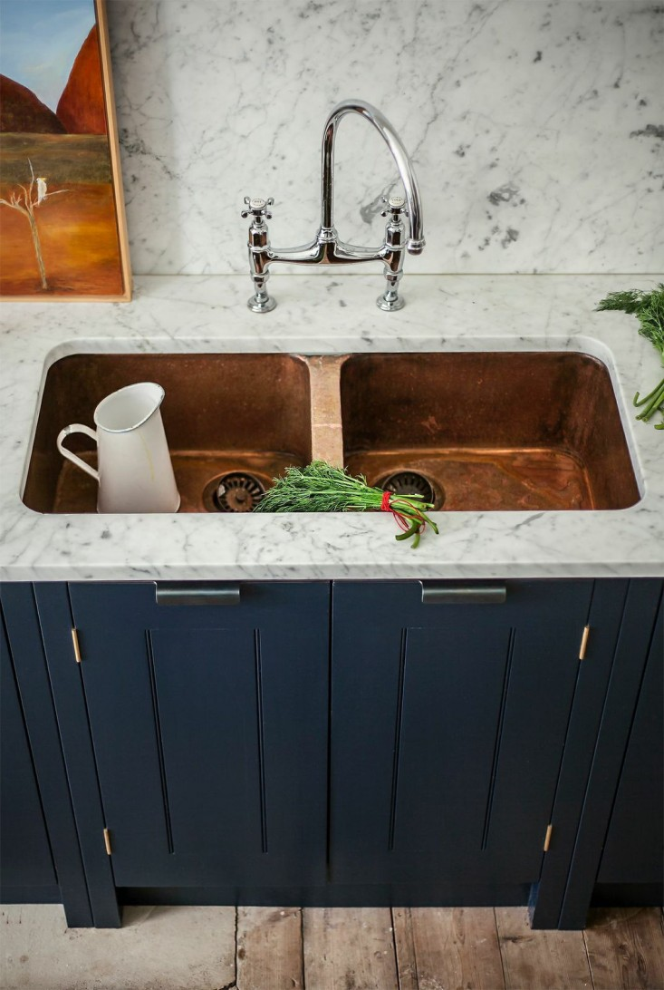 Moving away from - white or stainless sinksToward - composite, concrete or copper sinks - According to Houzz, in 2018 we can expect a move toward using more dark-hued concrete, stone, copper, and granite composite sinks in place of the traditional white or stainless steel. I especially love the way the warmth of the copper sink sets off the coolness of the Carrera marble in this photo. That mixed with the blue cabinets creates that warm yet modern vibe.