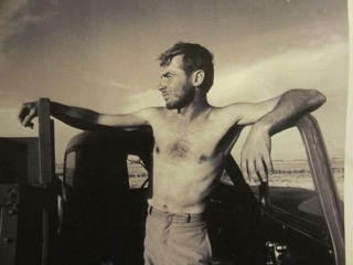 An old photograph of a young Richard, shirtless, leaning against the door of a pickup, gazing thoughtfully into the distance against an open sky.