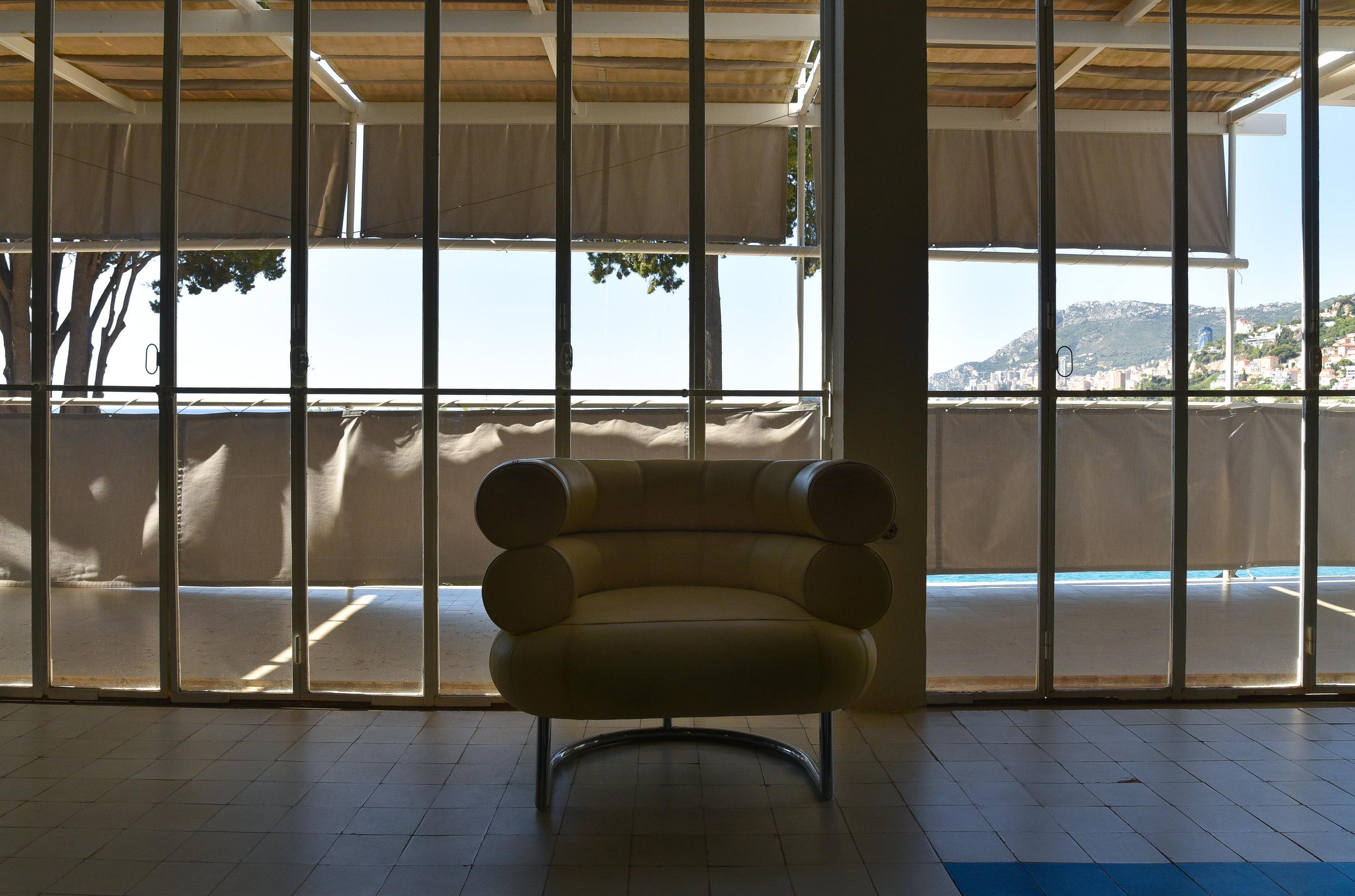 sea views through a glass walL AND  BIBENDUM  CHAIR