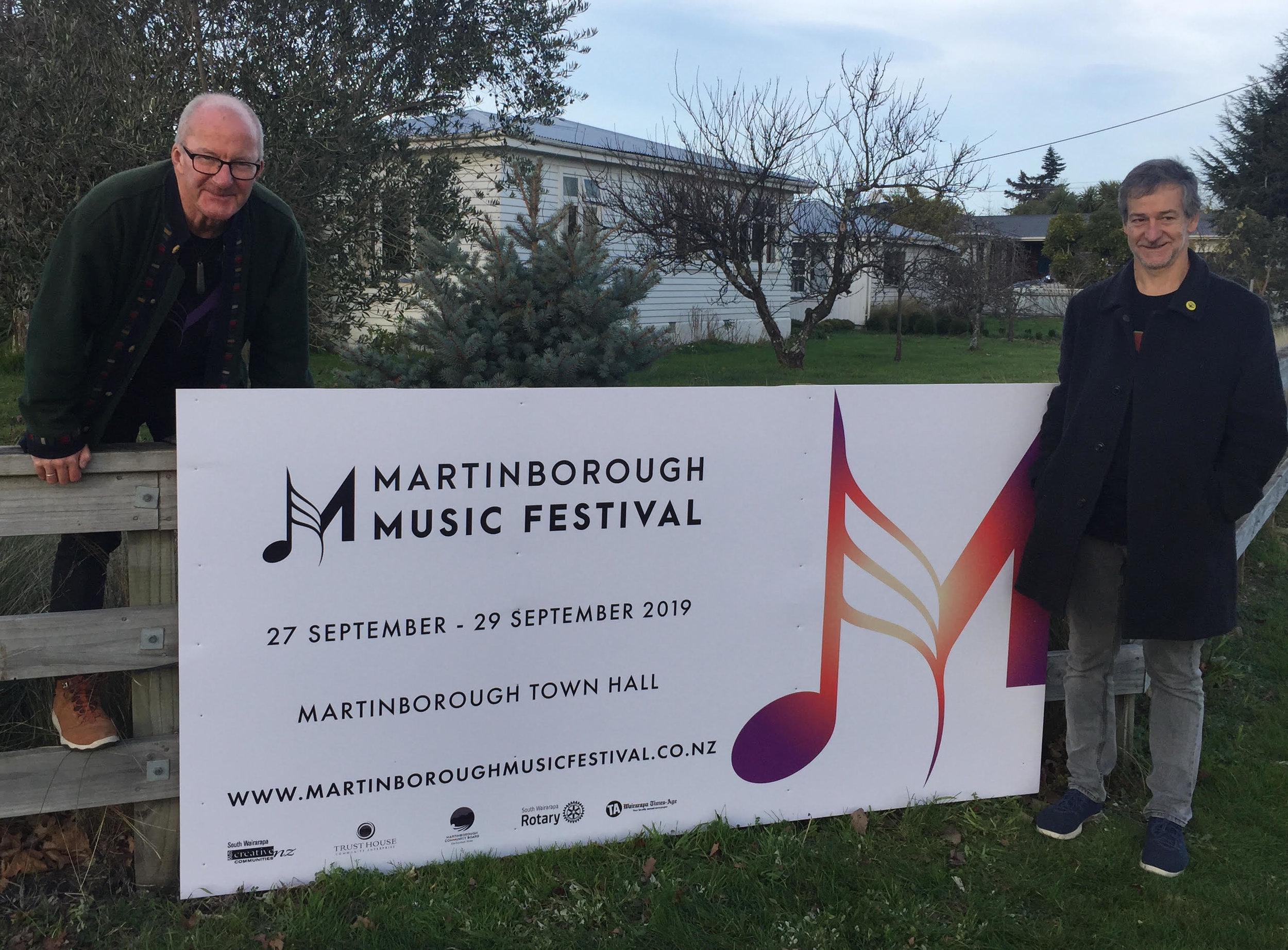 The 2019 sign goes up on the corner of Kitchener and Princess to welcome visitors to Martinborough. With Brendan Smyth (left) and Andrew Morrison … and thanks to Glenys Hansen for the fence.