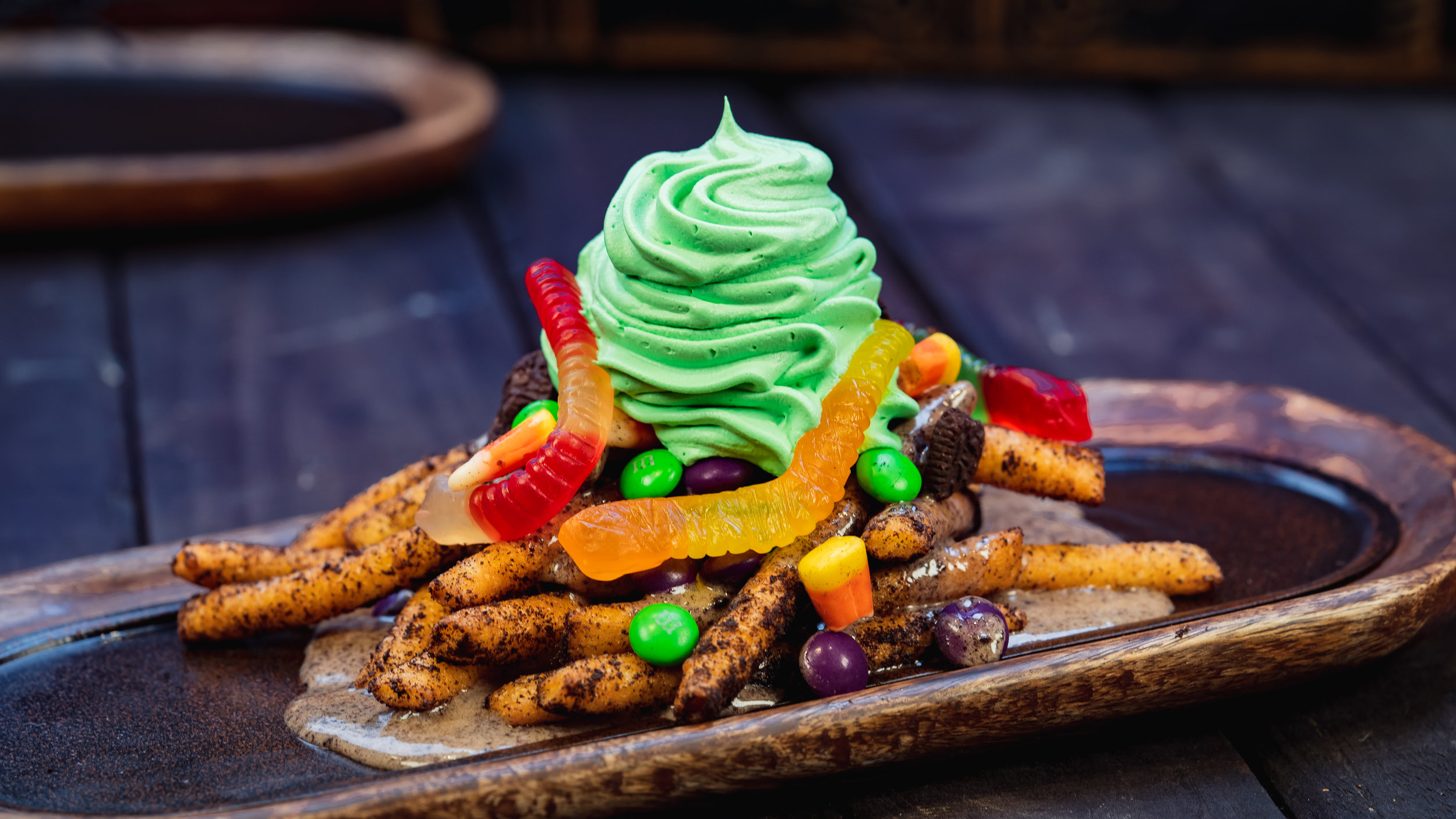 Disney guests will discover a variety of delicious treats during Halloween Time at Disneyland Resort, from Sept. 6 through Oct. 31, 2019. At Award Wieners at Disney California Adventure Park, guests will find these Oogie Boogie-inspired funnel cake fries dusted in crushed chocolate cream cookies, topped with cream cheese sauce, chocolate cream cookie pieces, gummy candies, chocolate coated candies and whipped cream. (David Nguyen/Disneyland Resort)