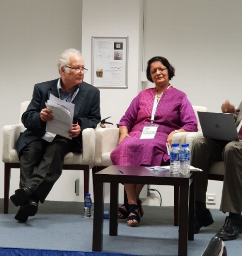 Founder Meera Shenoy on the panel at the UNESCO workshop. She wears a magenta tunic and white conference badge, sitting between two men in black suits.