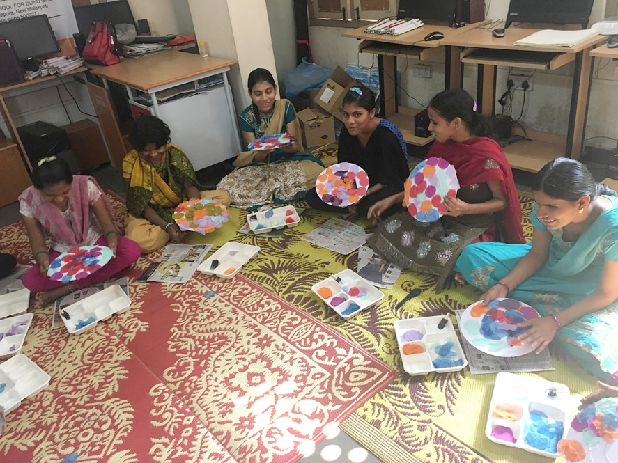 Six girls sit on a red and yellow patterned mat, assessing their nearly-finished artwork.