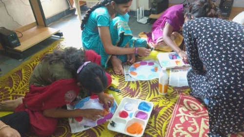 Three girls sit on a yellow and purple patterned mat, working on their boards. The NJA instructor kneels in front of the girl on the far right, guiding her hand toward her tray.