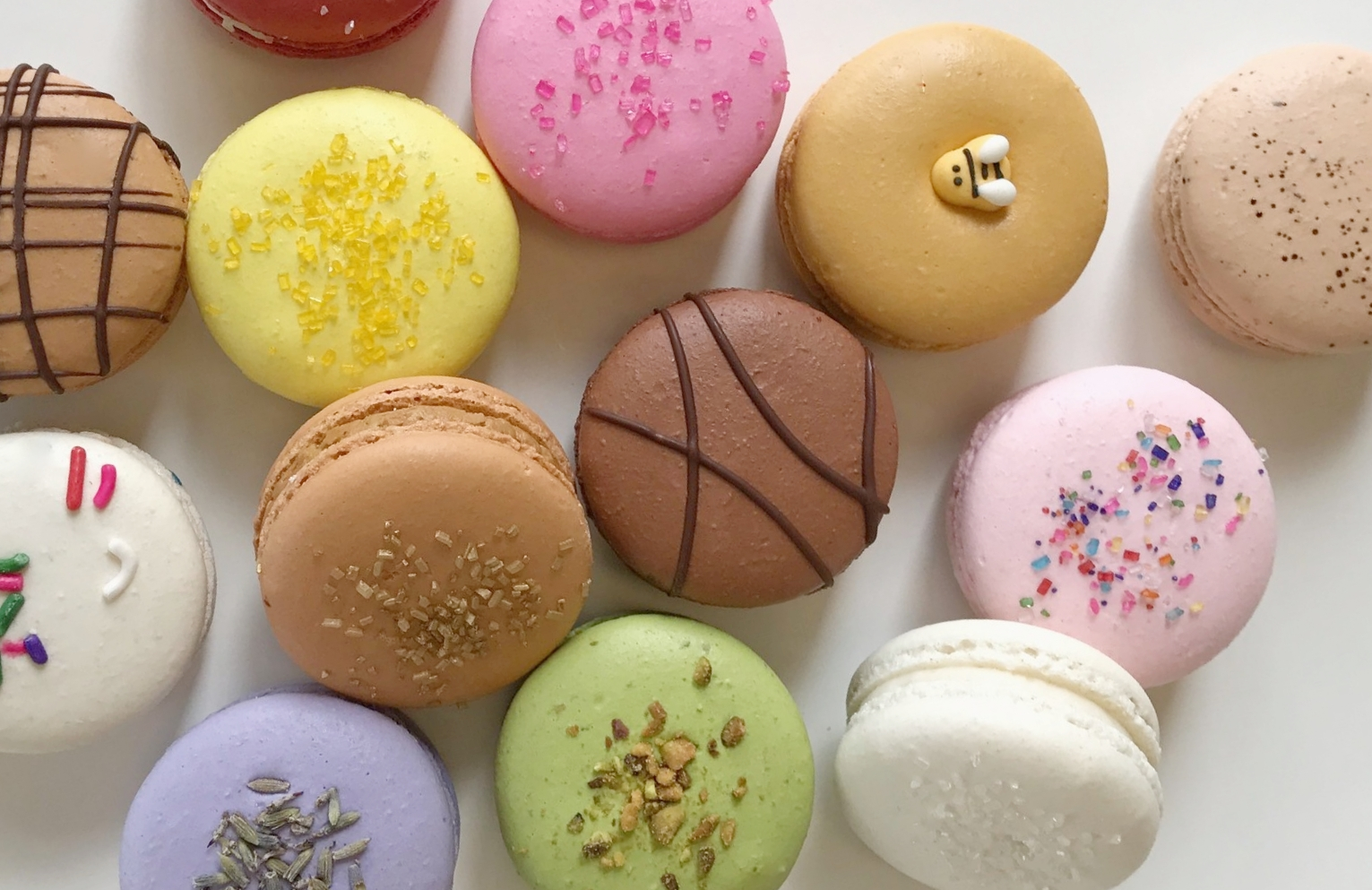 MACARON: ma·ca·ron \ mä-kə-ˈrōnn. a light, often brightly colored sandwich cookie consisting of two rounded disks made from a batter of egg whites, sugar, and almond flour surrounding a sweet filling, usually a ganache, buttercream, or jam. -