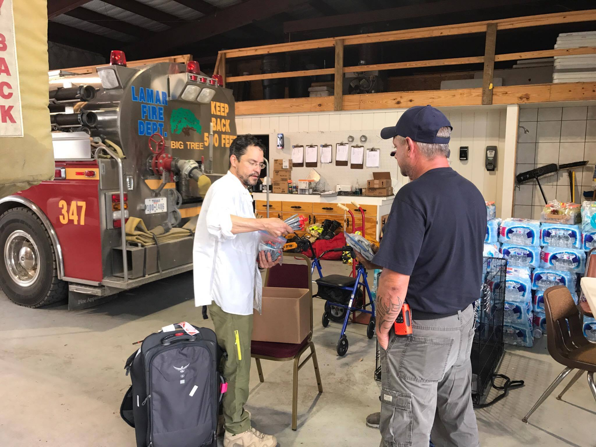 Eduardo Dolhun giving dripdrop to Lamar Volunteer Fire Department.jpg