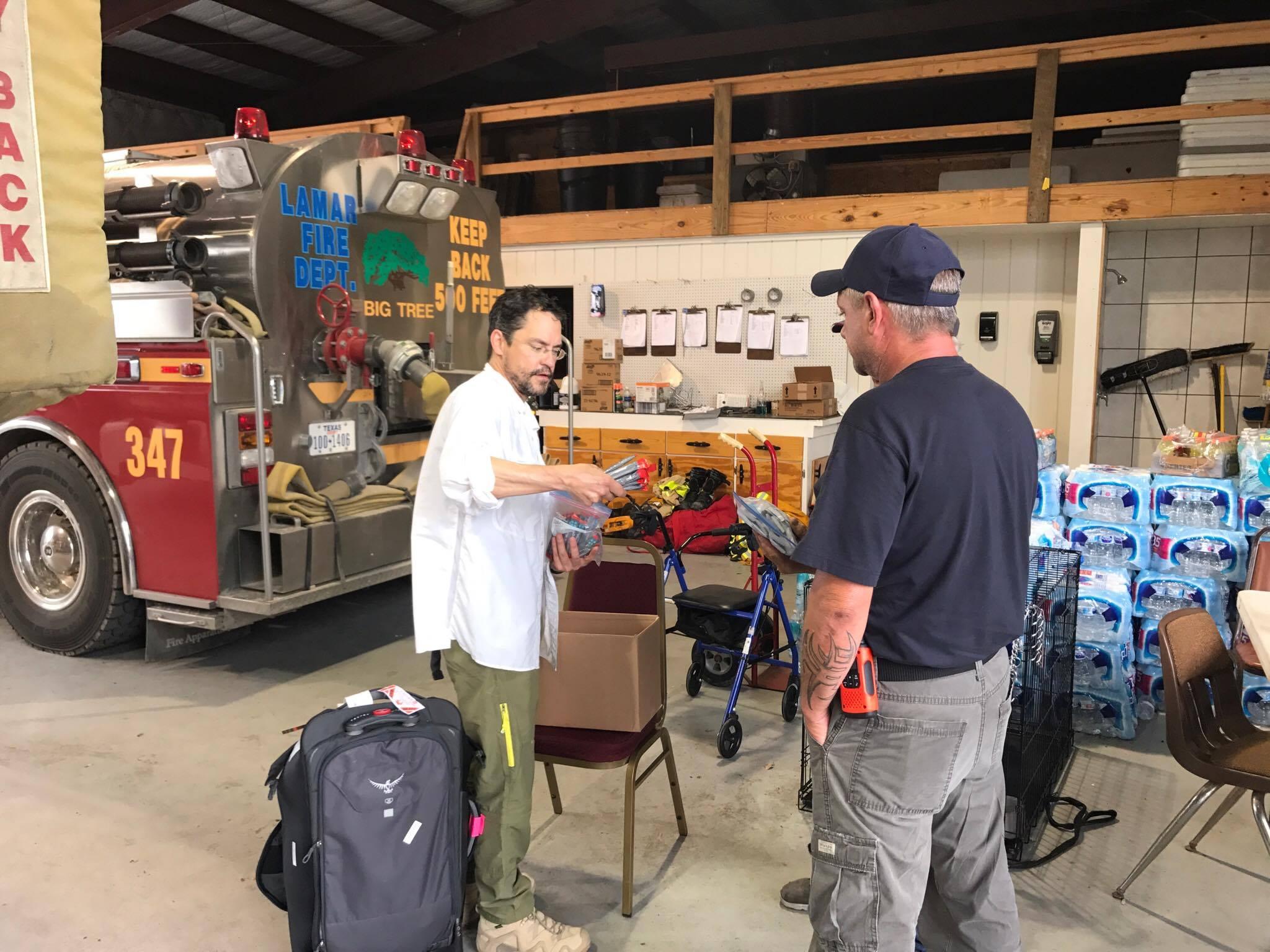 Eduardo Dolhun giving dripdrop to Lamar Volunteer Fire Department.jpg