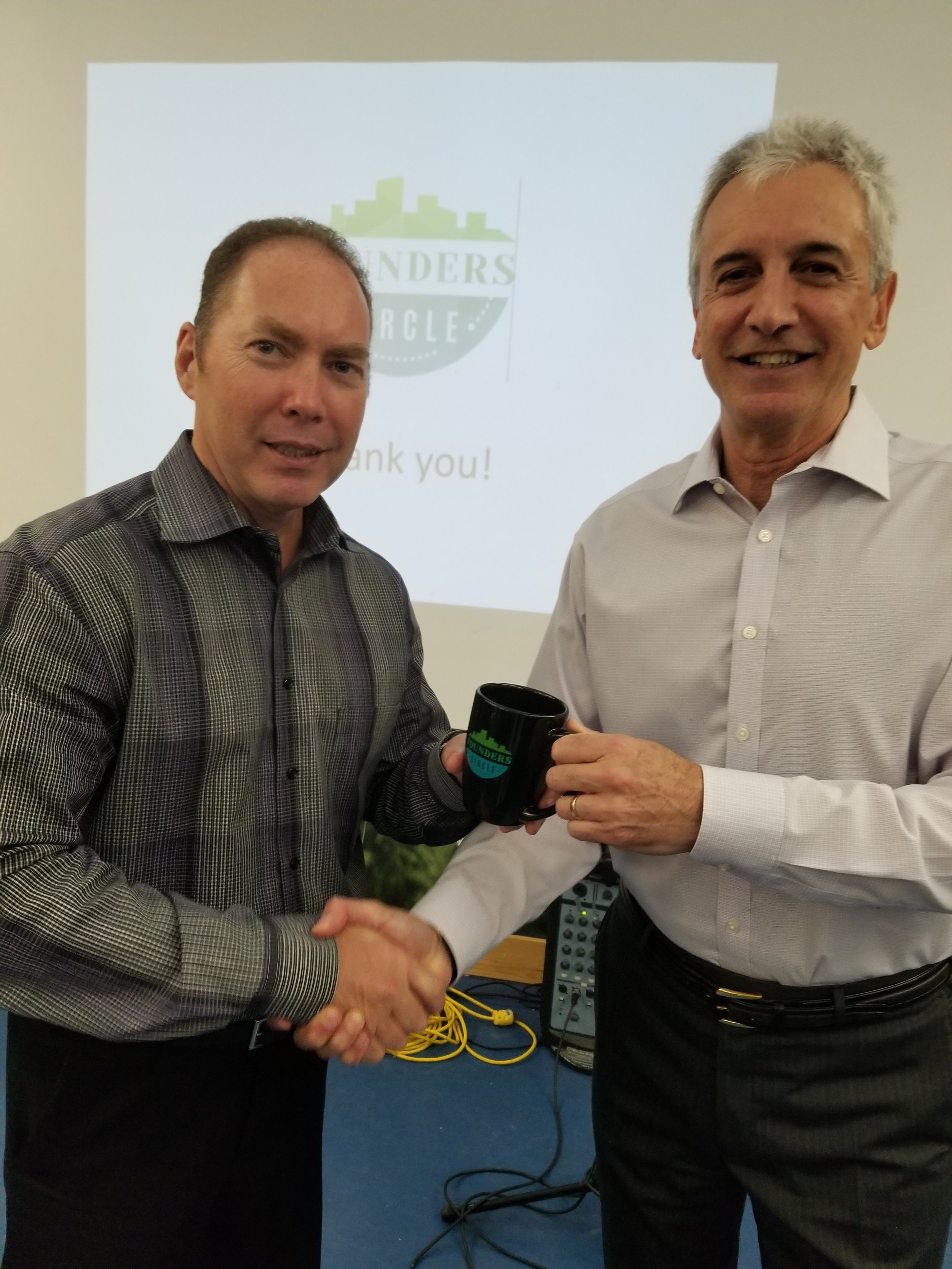 Karl Smith from Scotiabank, and Gravenhurst Rotary Club rep on Founders Circle receiving a Founders Circle gift mug from Executive Chair Rick Dalmazzi after Rick provided a presentation to the Rotary Club on the results of the first year of Founders Circle.