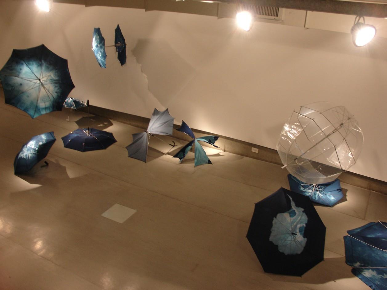 Installation de 36 parapluies modifiés avec le procédé photographique du cyanotype. Galerie Arte X Arte, Buenos Aires, Argentine