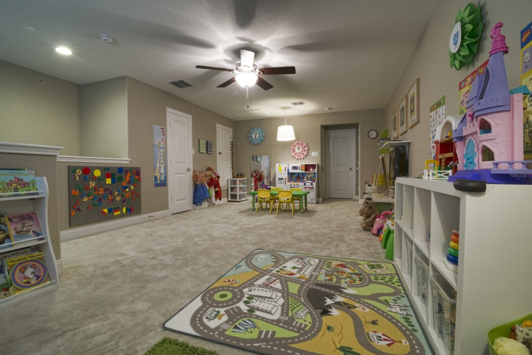 "The kids domain. The two small windows and single overhead light fixture made this giant space entirely too dark so we brightened it up in zones: a ""kitchen"" light in the play kitchen area and a ""reading lamp"" in the reading nook."
