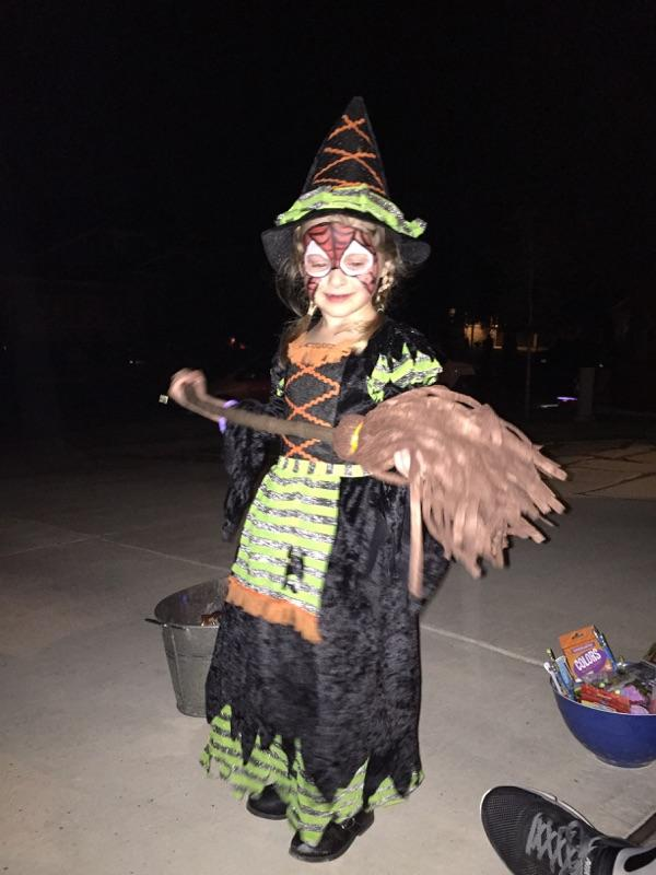 Having fun handing out candy...she didn't want to wash off her spiderman face paint fromt he fall festival so she was a spider-witch!