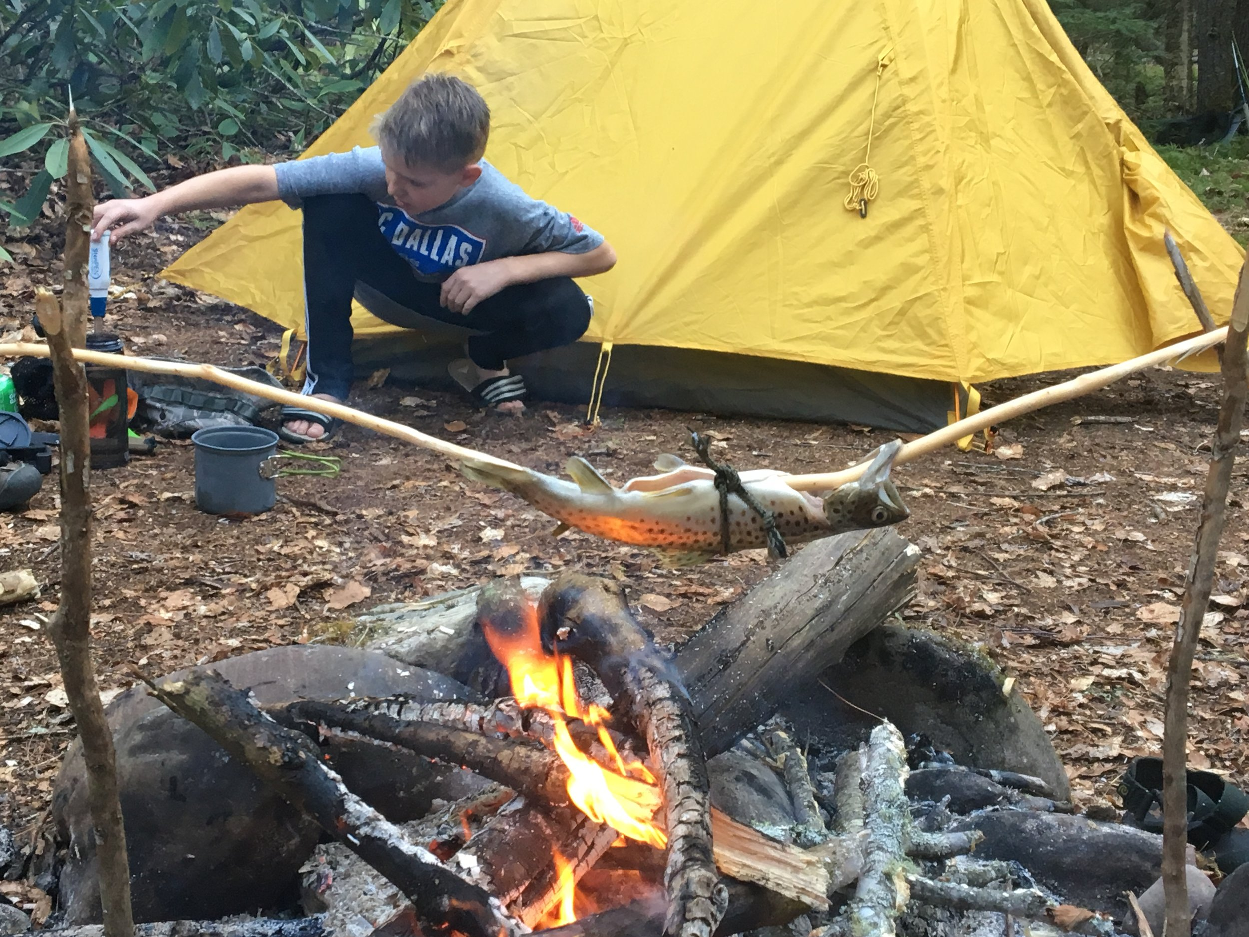 My son, Braeden, cooking a trout over the fire.