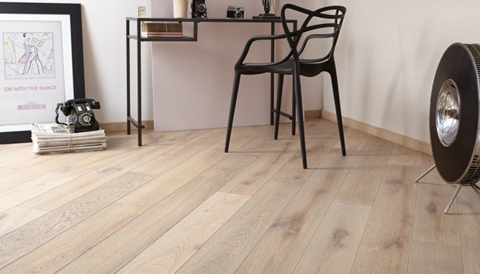 diagonal-wood-floor-installation-with-round-floor-accessory-and-black-wooden-chair-facing-small-table-near-framed-picture.jpg