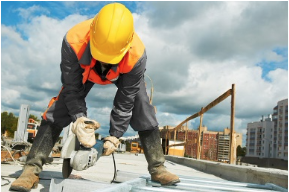 A construction worker in a hard hat on the roof of a building with an electric hand saw.