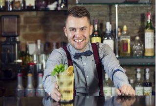A bartender in a bow tie serving a mixed drink.