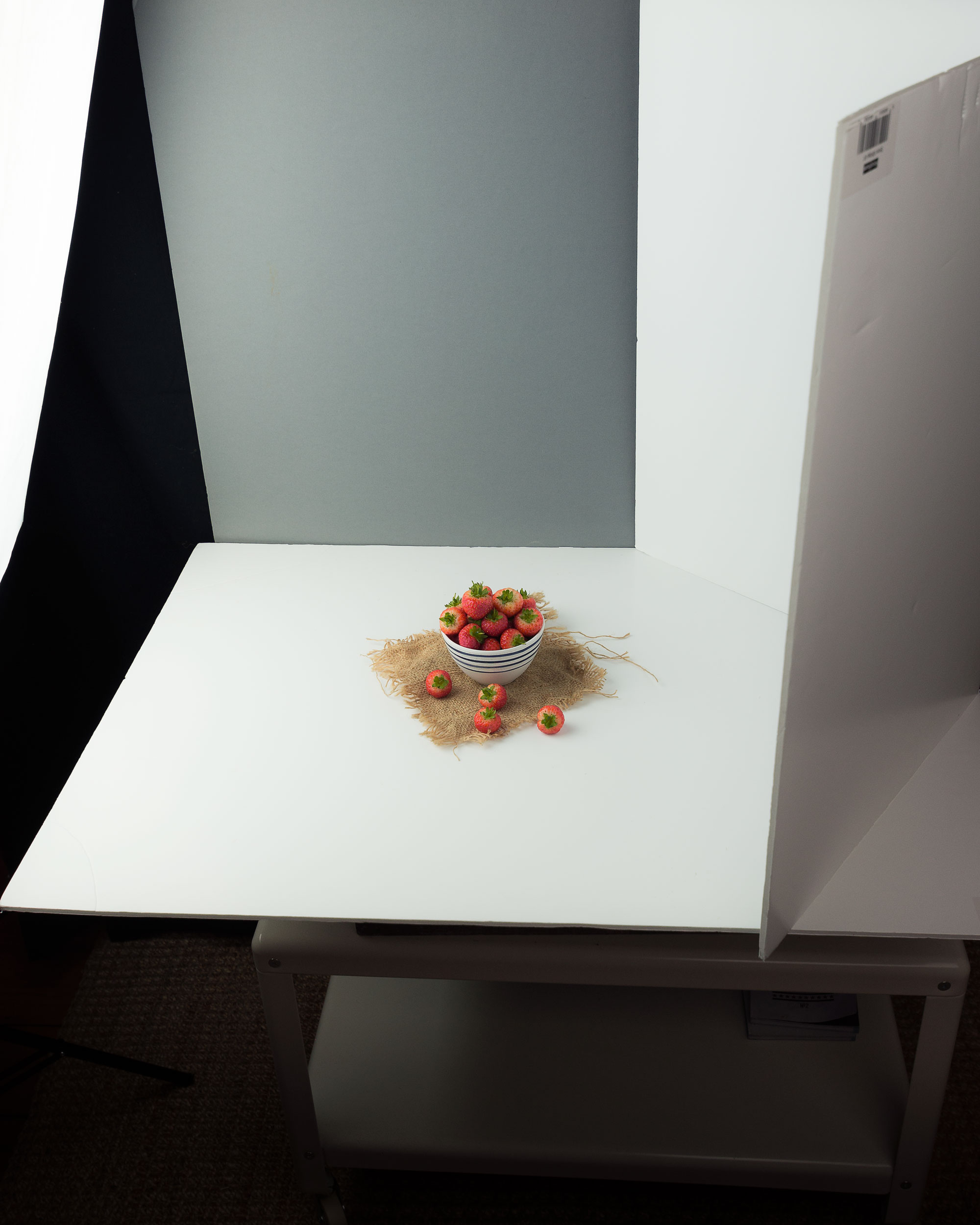 BTS of the strawberries shot above. I positioned a single soft box on the left hand side on 4/5ths power. The base card is semi gloss which reflects some of the light onto the underside of the strawberries and the bowl. On the right hand side I have a white semi gloss bounce card, folded to create two 45° angles. This bounces the light from the soft box back onto the front and back of the subject. I find this set up helps to create a more natural outdoor look with less shadow and contrast. The backboard is a soft grey bounce card, I edited this in post to have a bluer hue reminiscent of the sky. The small piece of hessian sack is used to create interest and I added a spoon to give the final image an anchor. I often find that the more simple the set up the stronger the final image is and this shot is definitely a good example of that philosophy.    Soft Boxes