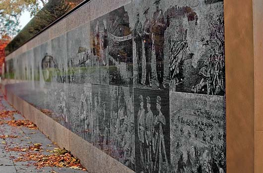 Veteran's Memorial – Queen's Park, Toronto   The monument is located on the northwest part of the front lawn at Queen's Park. It consists of a 100 feet long retaining wall clad in polished granite wall etched with scenes from Canada's war history as well as bronze inlay pieces designed by Allan Harding MacKay and inscribed with text contributions from author Jane Urquhart and military historian Jack Granatstein. As well, the monument features a stone-paved gathering area, a seating area, paths and gently sloping lawn.We undertook the design and detailing of the retaining wall and reinforced the concrete elements of the bench.  Photo Courtesy of The Ontario Realty Corporation