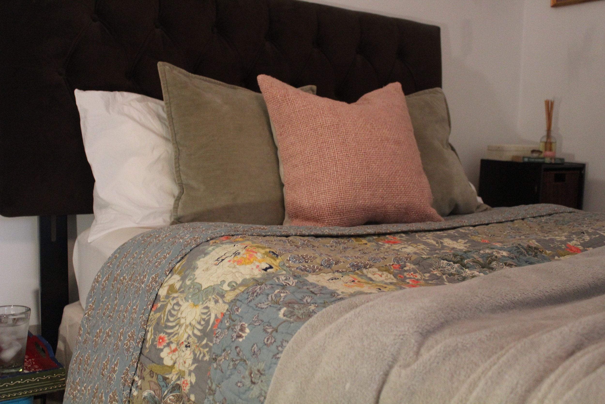 SUMMER - Start with a bright and colorful patchwork quilt and just add on one solid blanket for a relaxed look. The white sleeping pillows are behind two 20