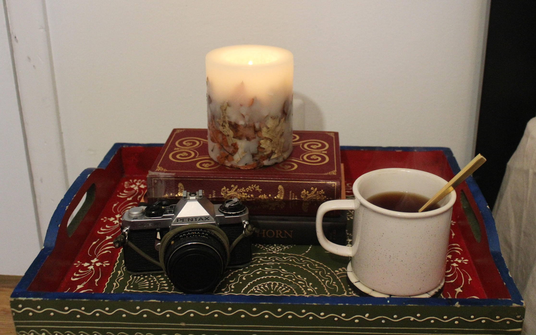 FALL - A harvest spice candle with leaves in it combined with a mug of warm tea on this bedside table emmulates fall and invites you to cozy up in bed.
