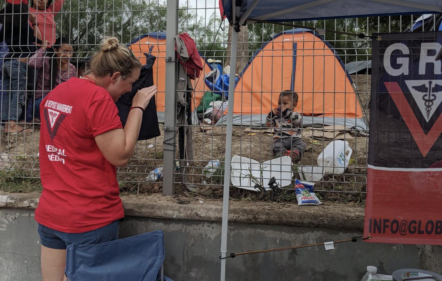 全球性回应管理人员通过在边境围墙的一个年轻的病人播放。