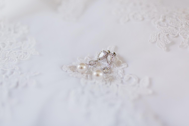 Bridal details of teardrop earrings laying on wedding gown