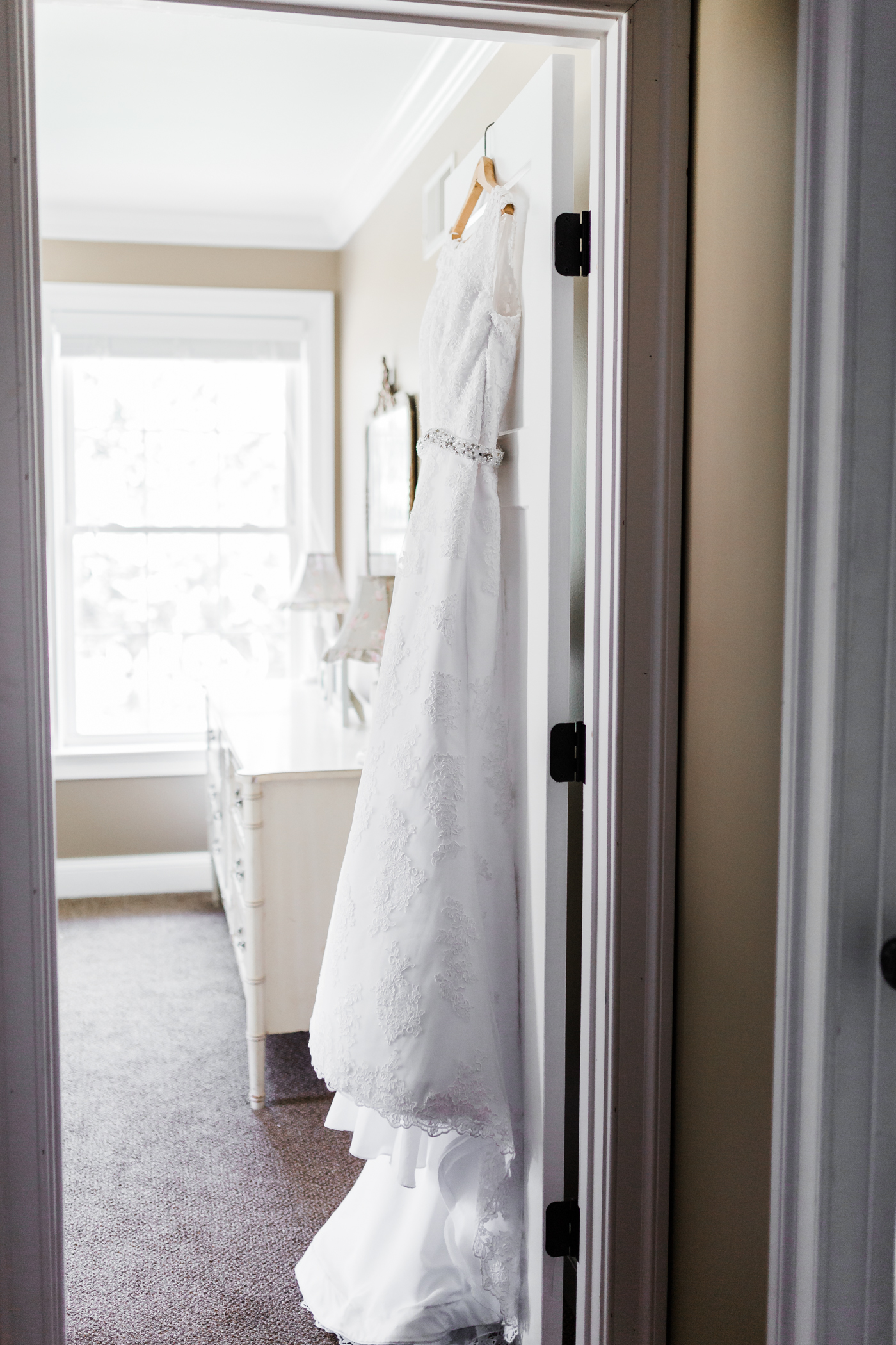 Wedding dress hanging on bedroom door for winter Maryland wedding