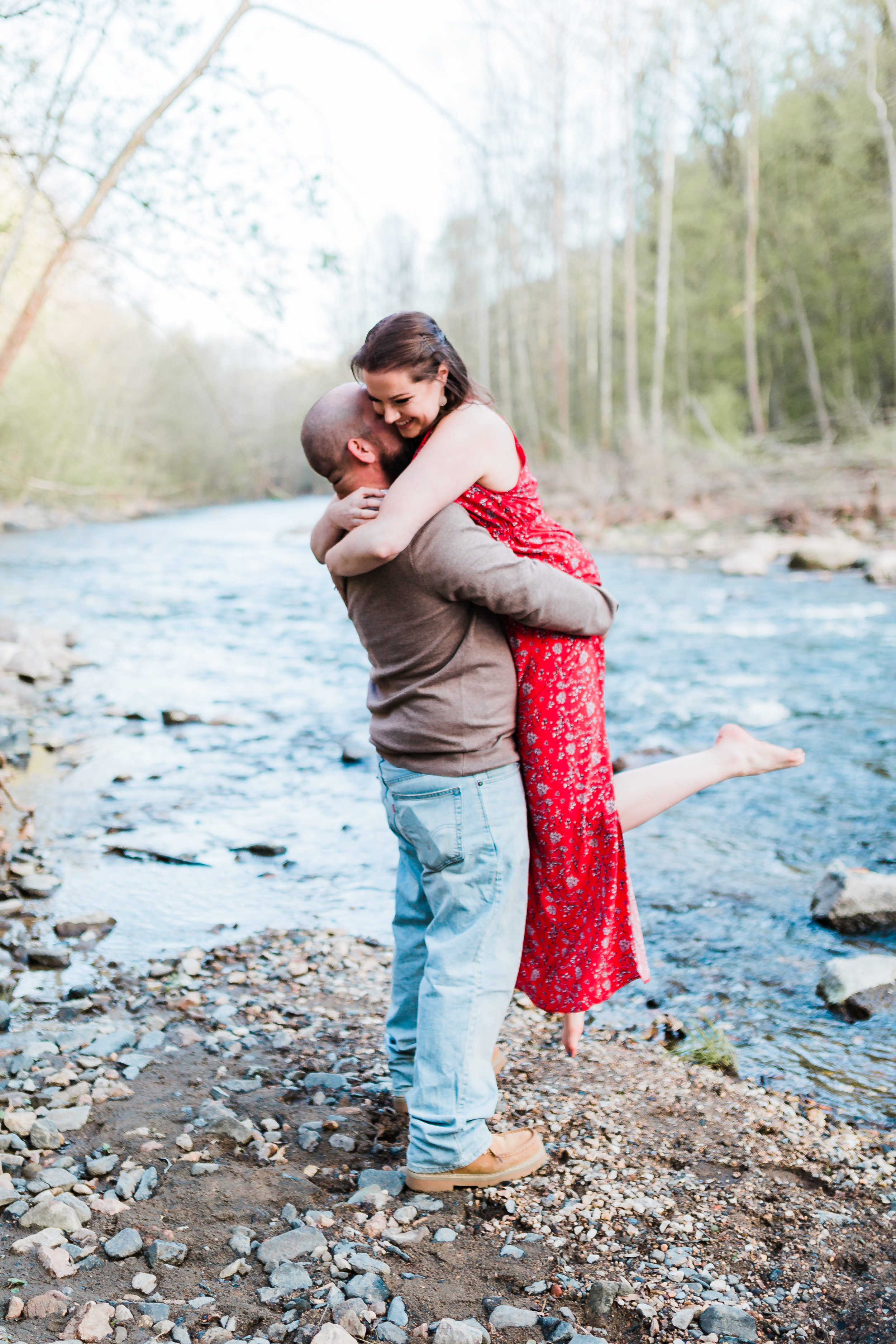 groom picking up bride and kissing her during their patapsco valley state park engagement session in maryland