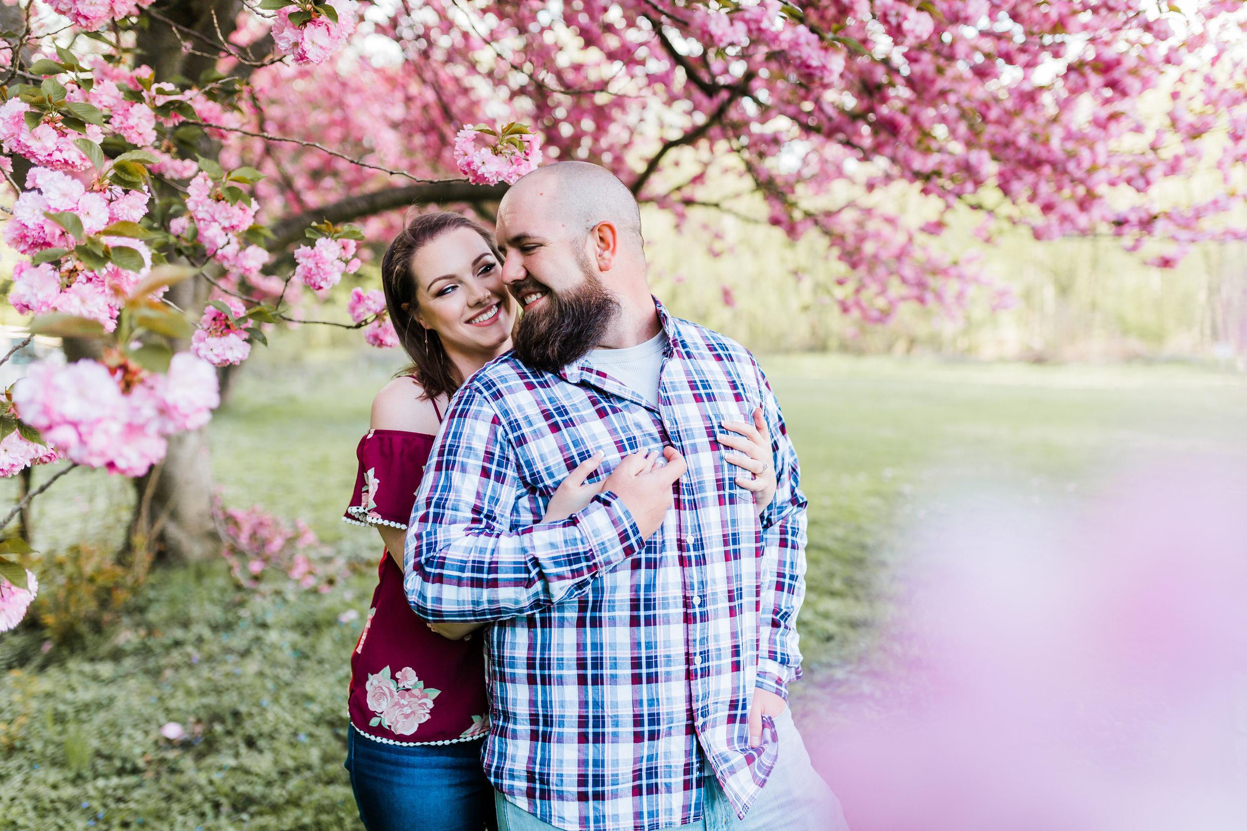 couple hugging under cherry blossoms in elkridge maryland