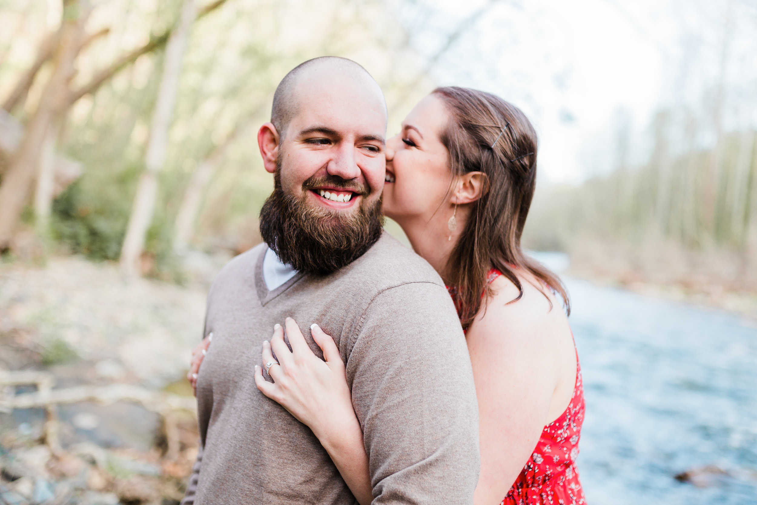 bride biting grooms ear and laughing at maryland engagement session - patapsco valley state park