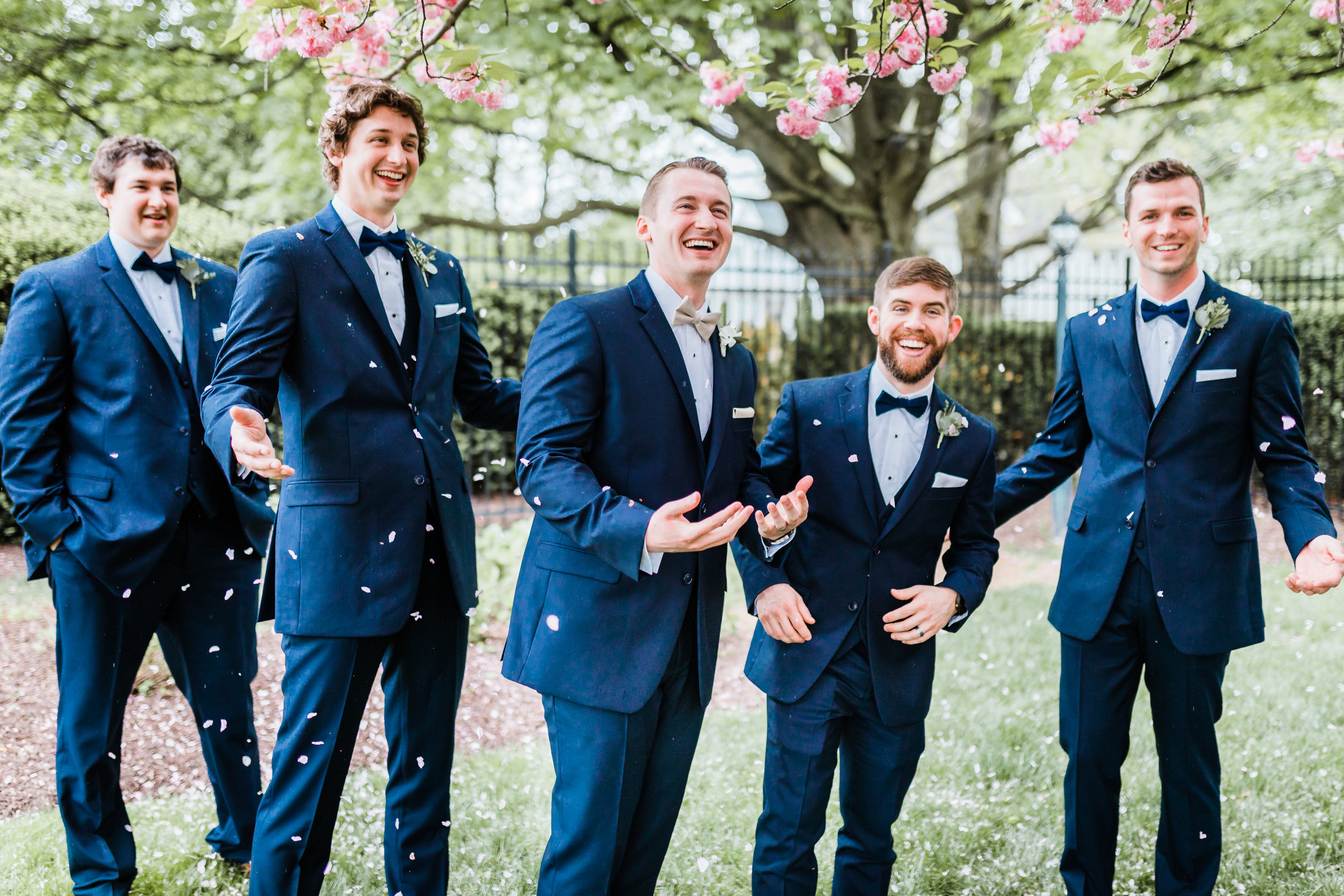 groom with his groomsmen laughing under cherry blossom tree