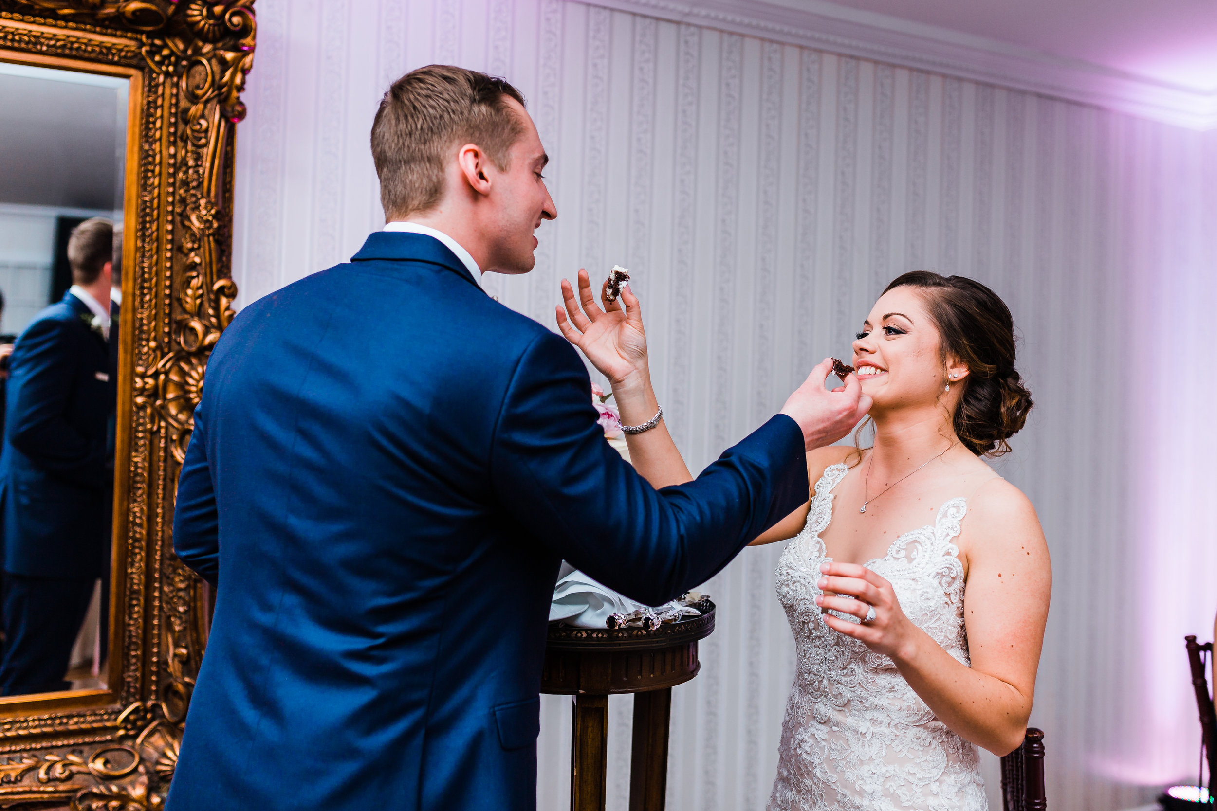bride and groom feed each other cake after cutting