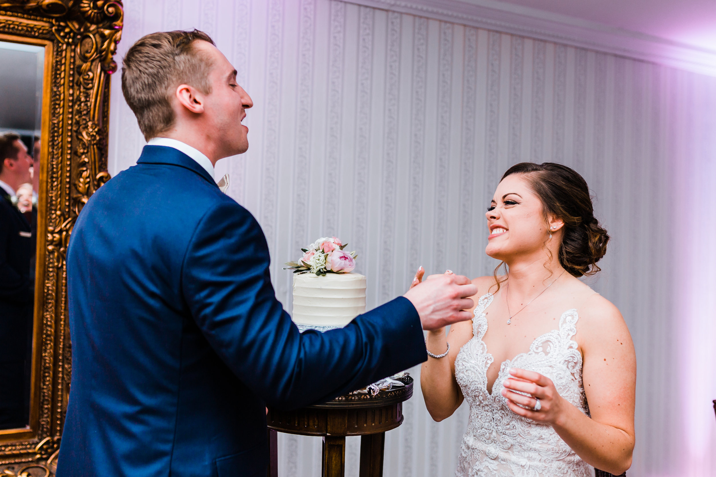 bride and groom laughing after feeding each other cake that their carroll county maryland wedding - photographer