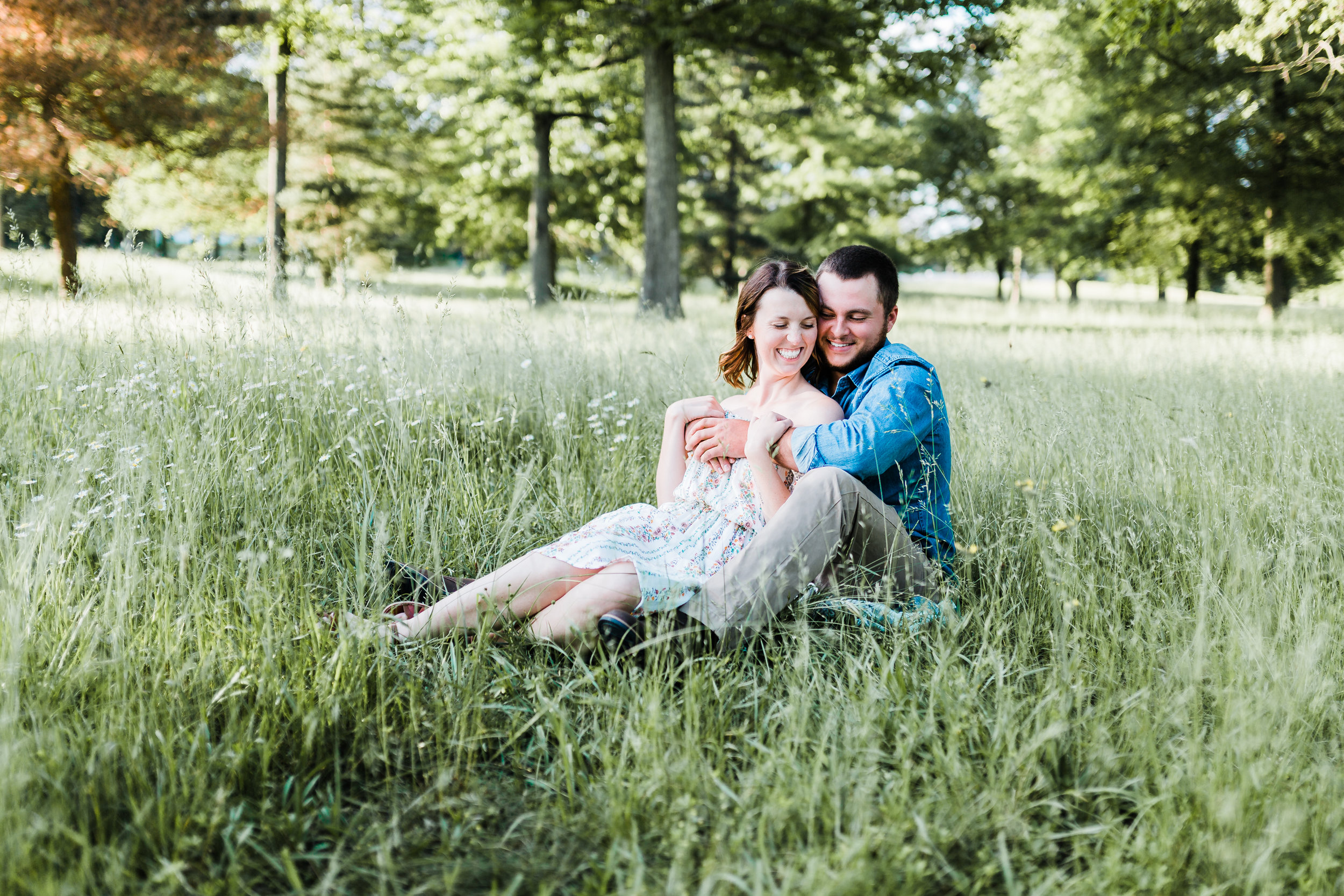 couple snuggling in tall grasses for engagement photos in maryland