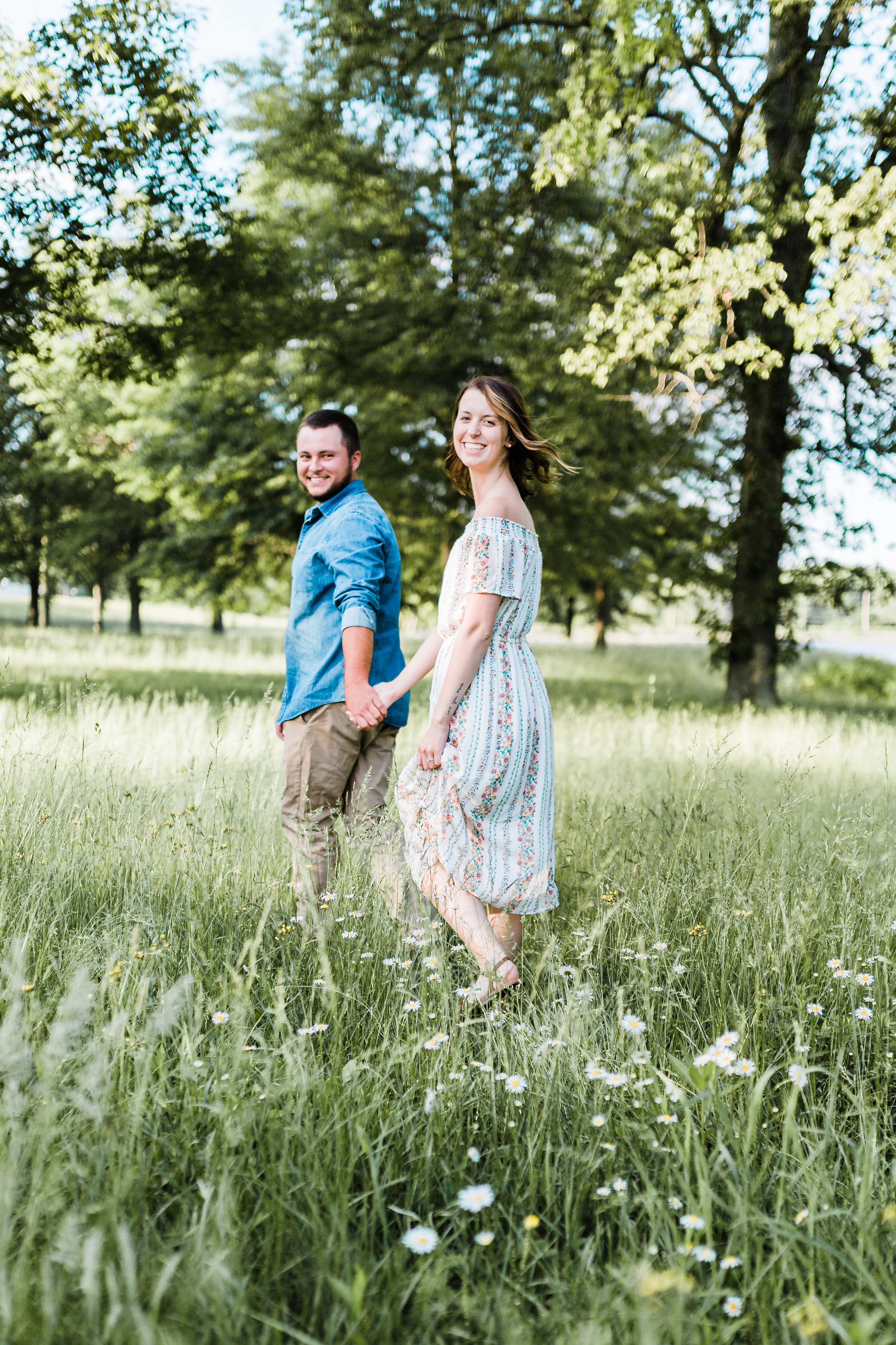 couple walking and laughing while holding hands - maryland engagement and wedding photographer