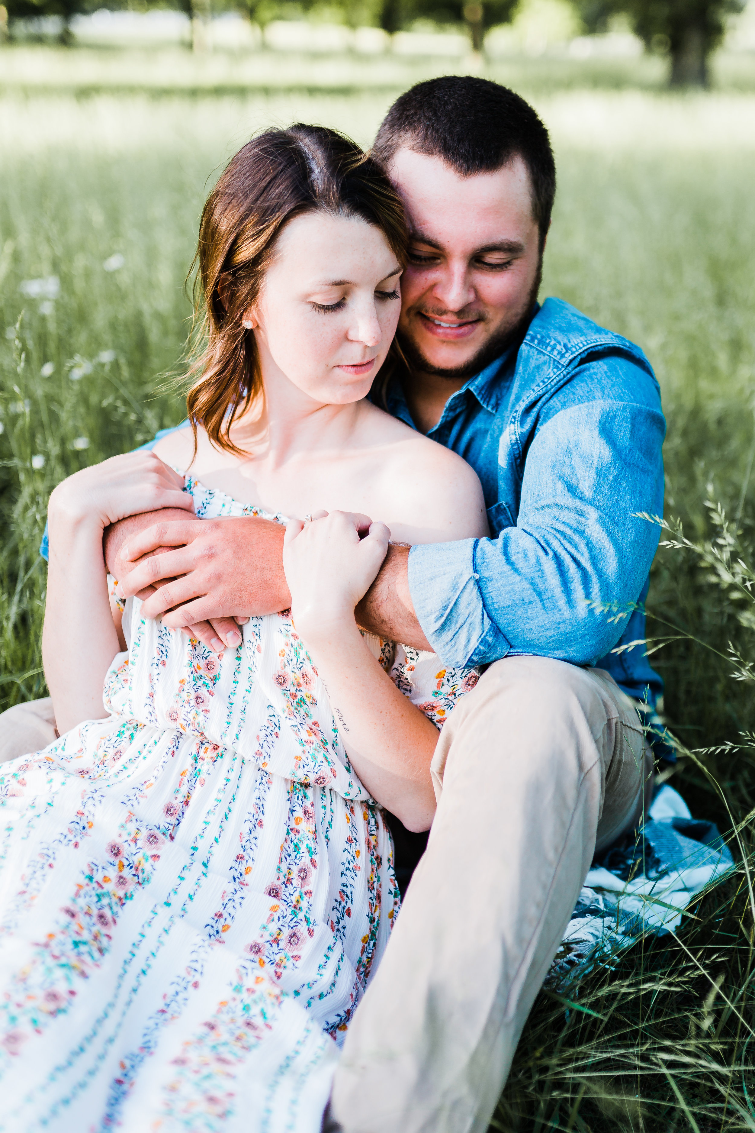 couple snuggling sitting down md engagement