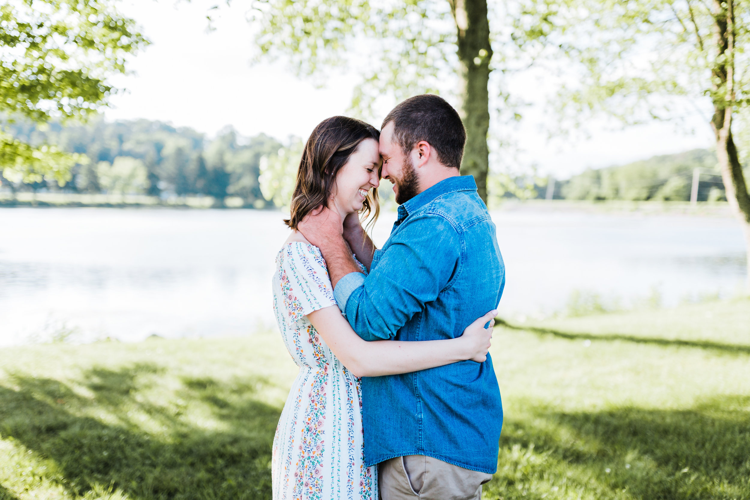 groom romantically holding his bride while they giggle at md engagement photo session