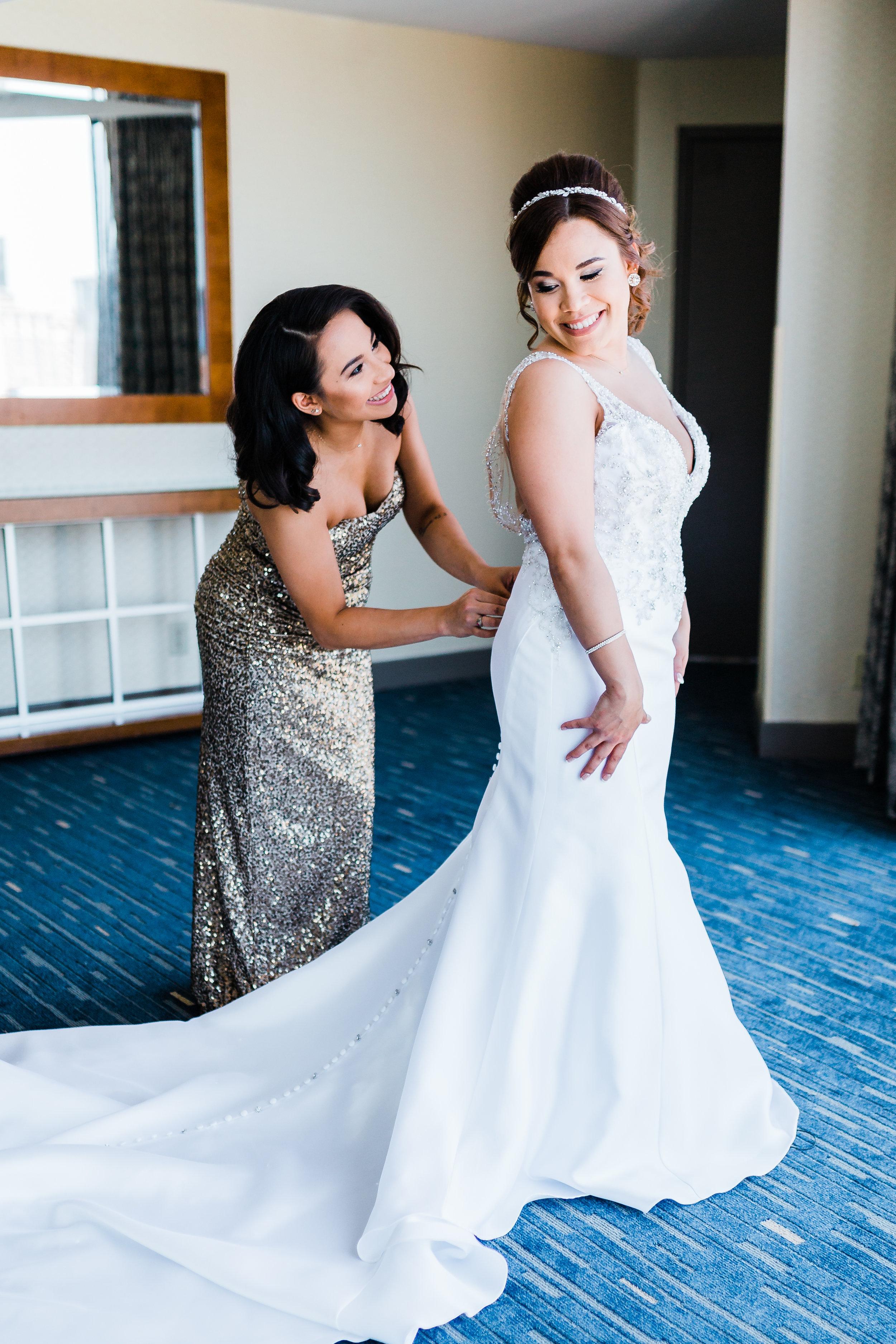 bride getting dressed at Hyatt Regency Baltimore MD wedding photographer and cinematographer