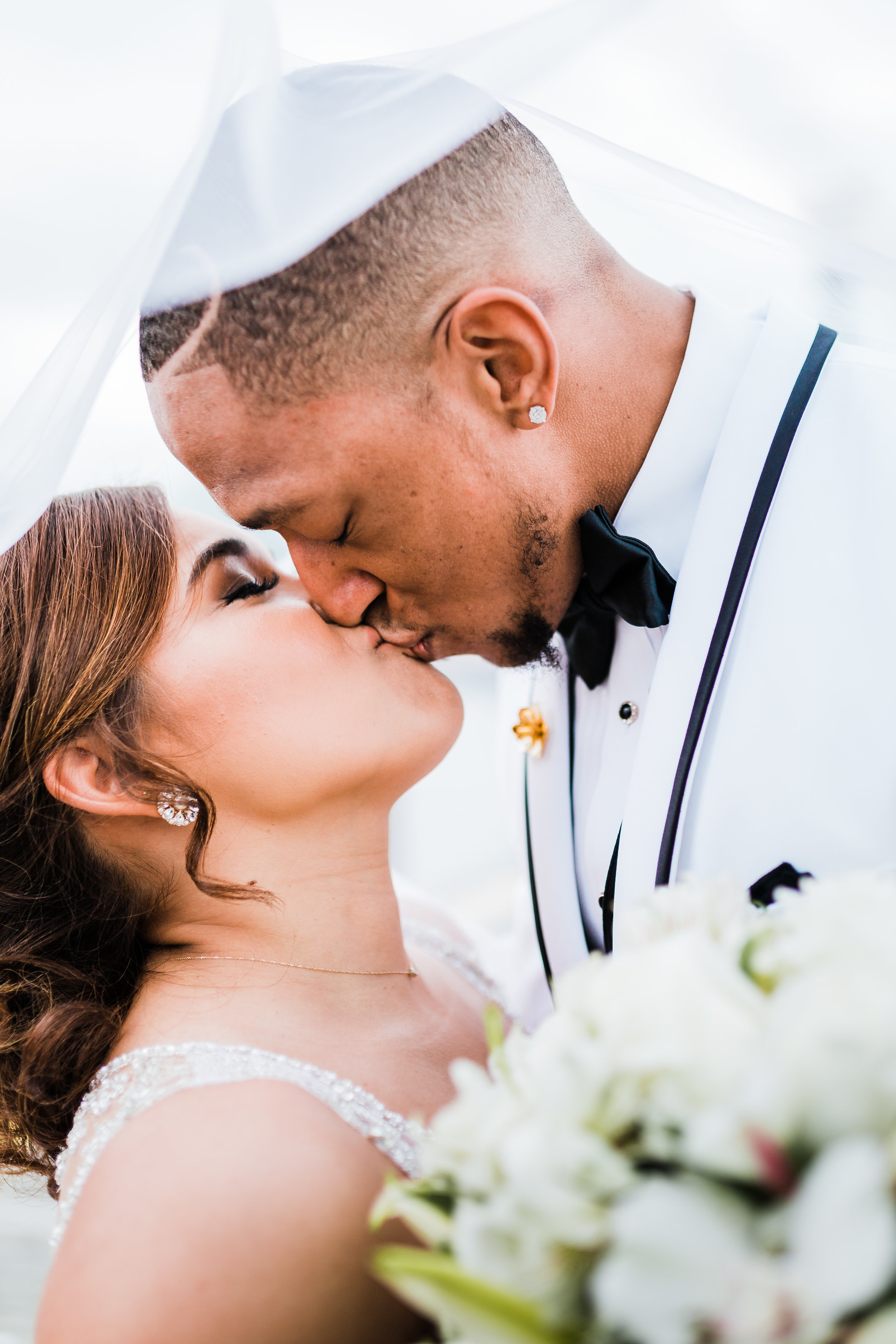 bride and groom kissing under veil on dock in baltimore maryland