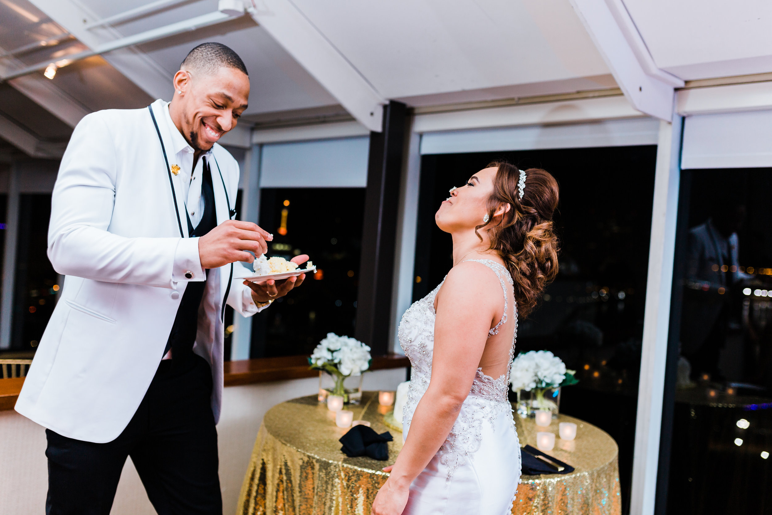groom puts some icing on bride's nose