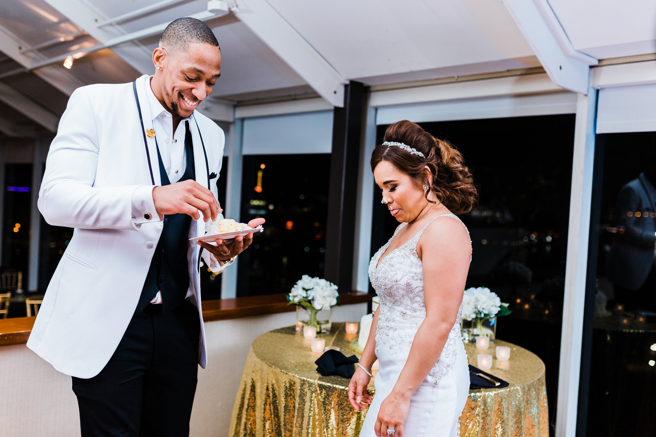 groom laughs after putting icing on bride's nose