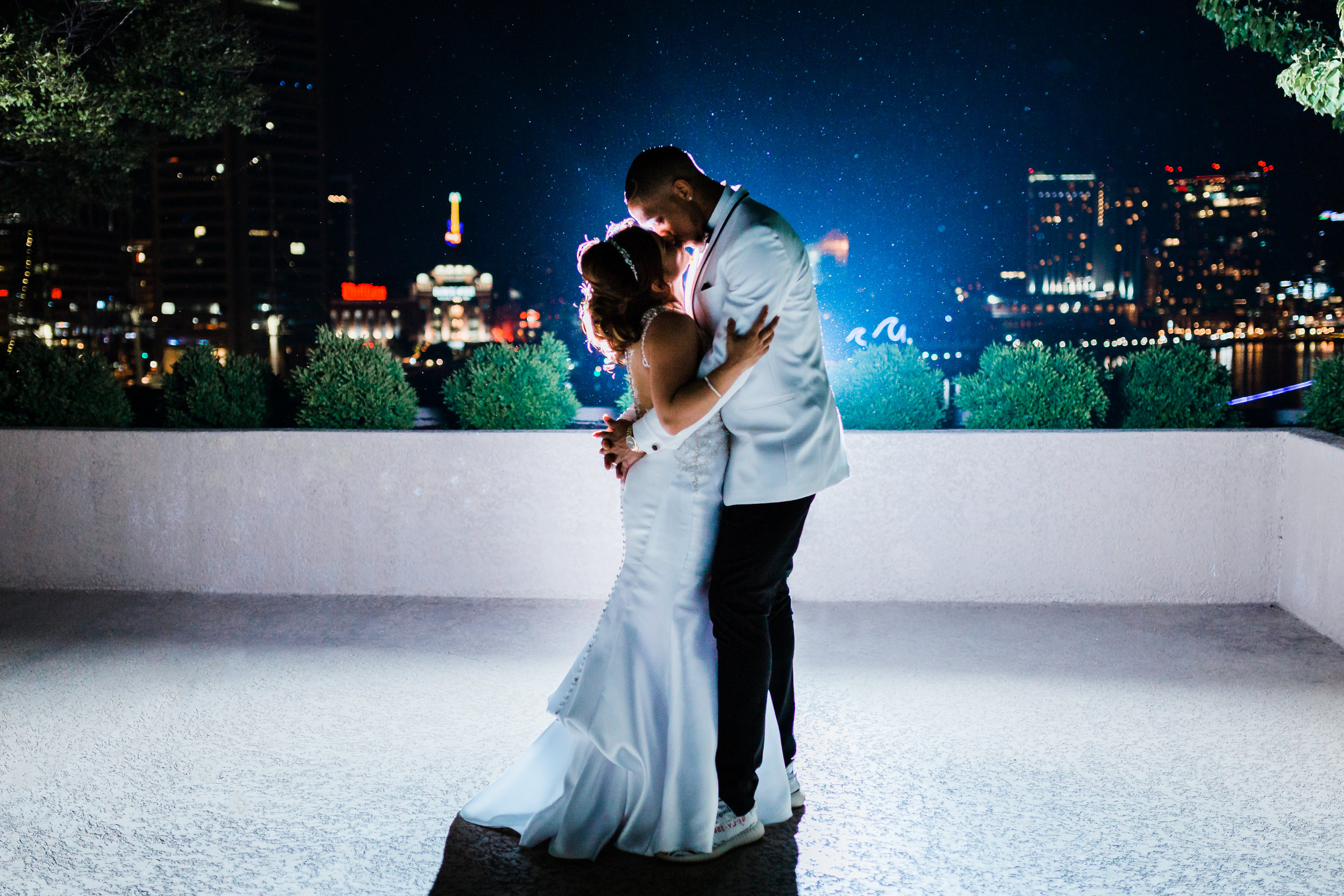 bride and groom kiss with city skyline in the background - maryland wedding photographer