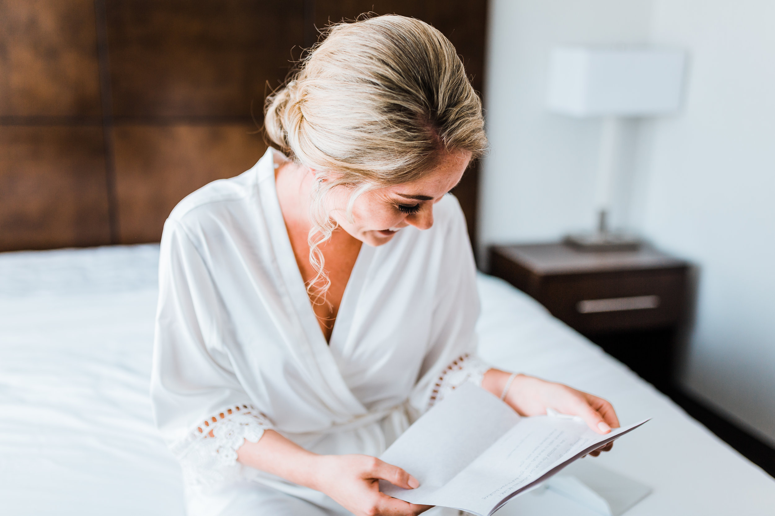bride in her hotel room getting ready and reading a letter from her groom - maryland wedding photographer
