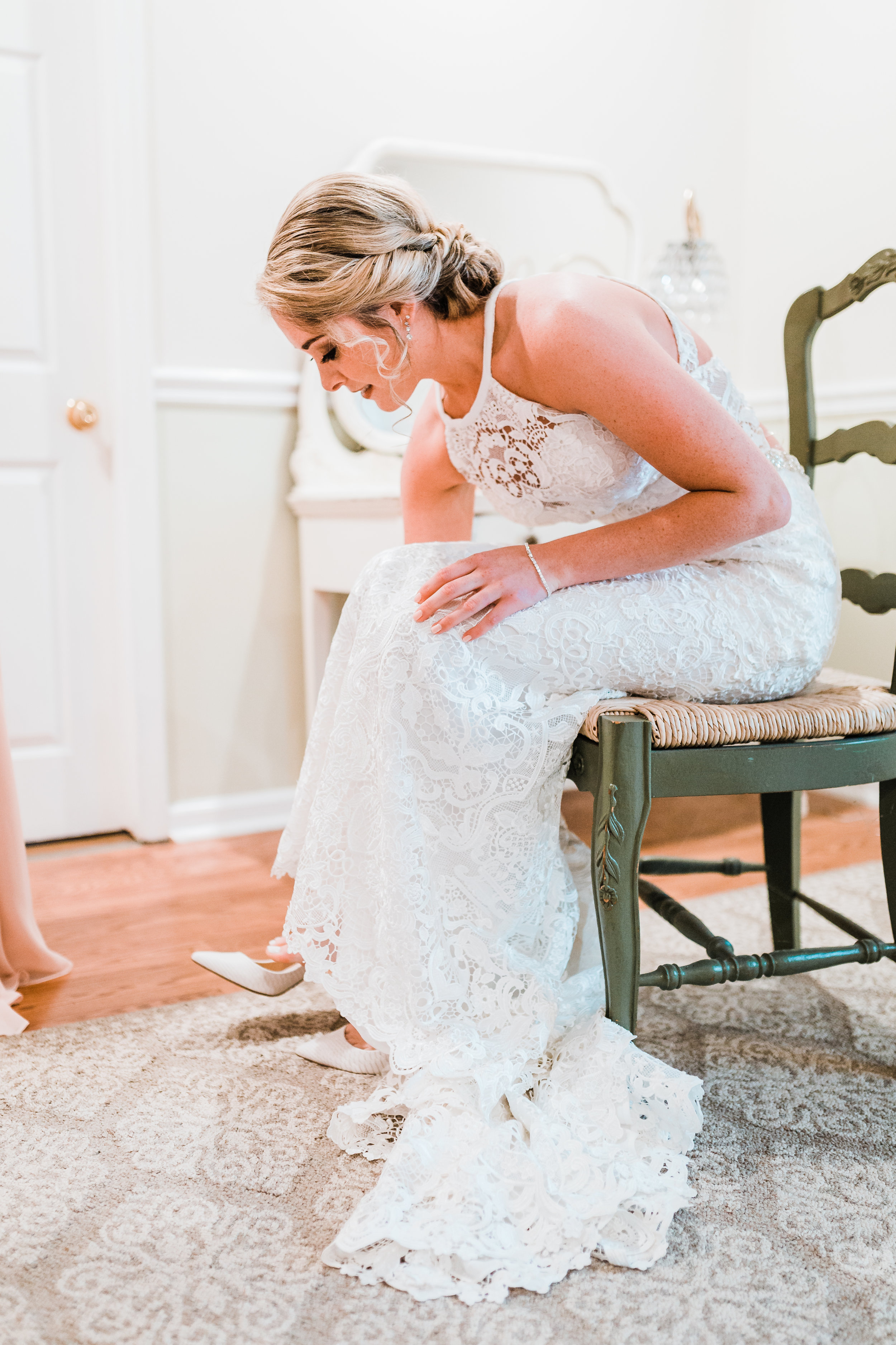 bride putting her shoes on at celebrations at the bay - maryland wedding photographer