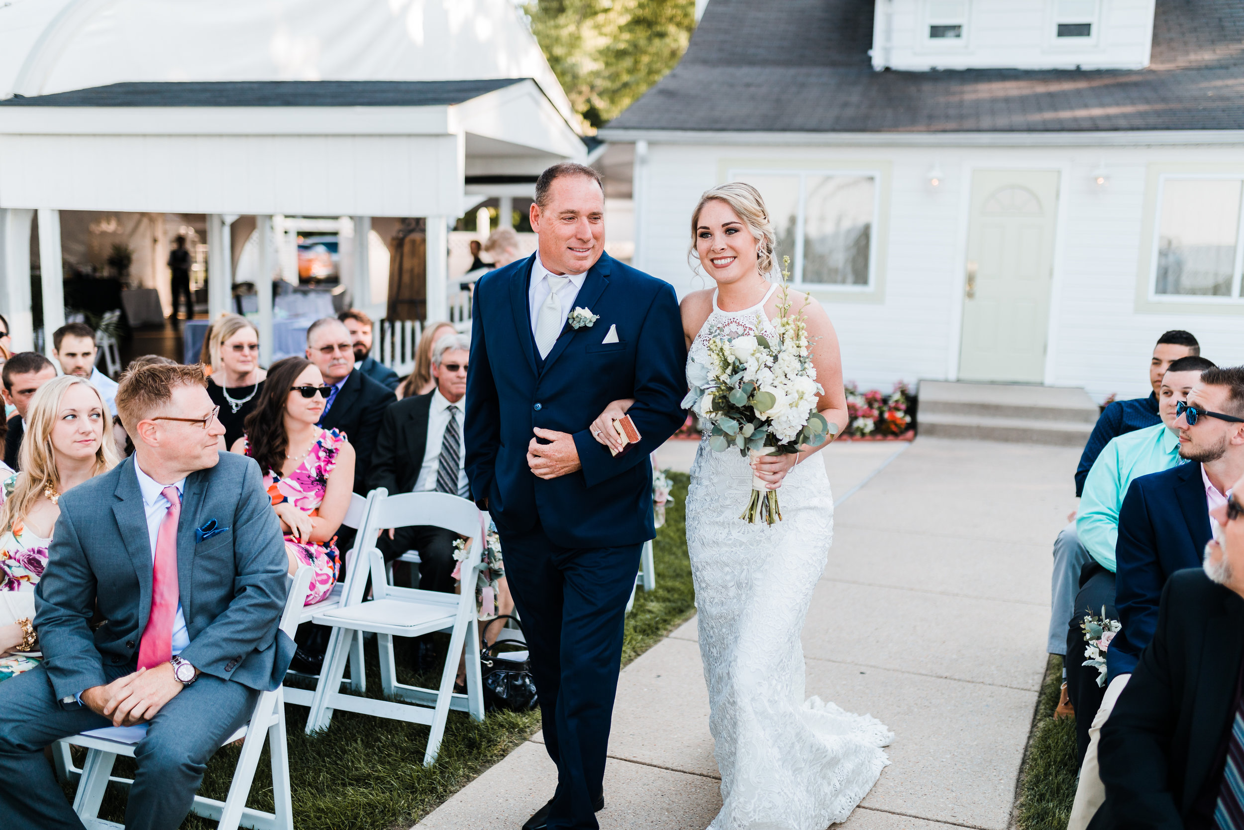 bride walking down the aisle with her father in high neck wedding dress with silver dollar eucalyptus bouquet at pasadena maryland wedding