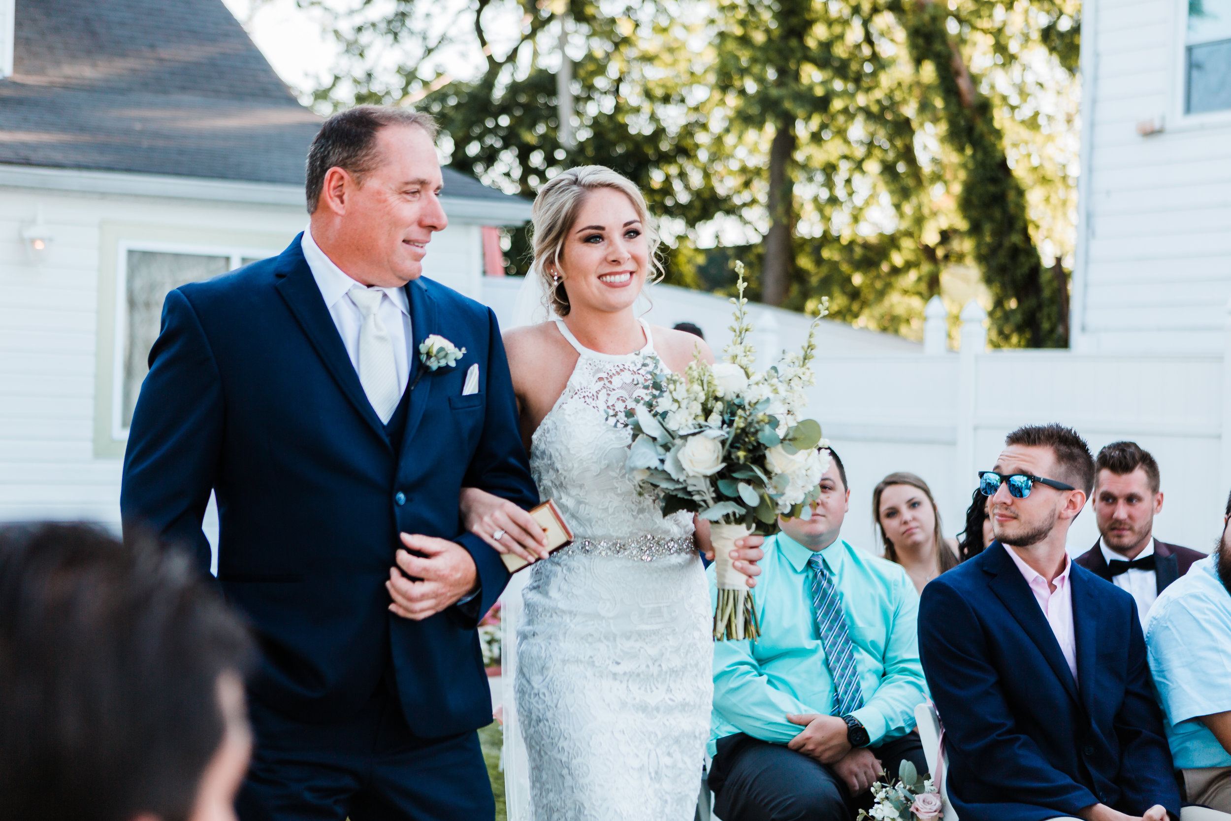 another angle of bride walking down the aisle with her father at celebrations at the bay - md wedding photographer and cinematographer
