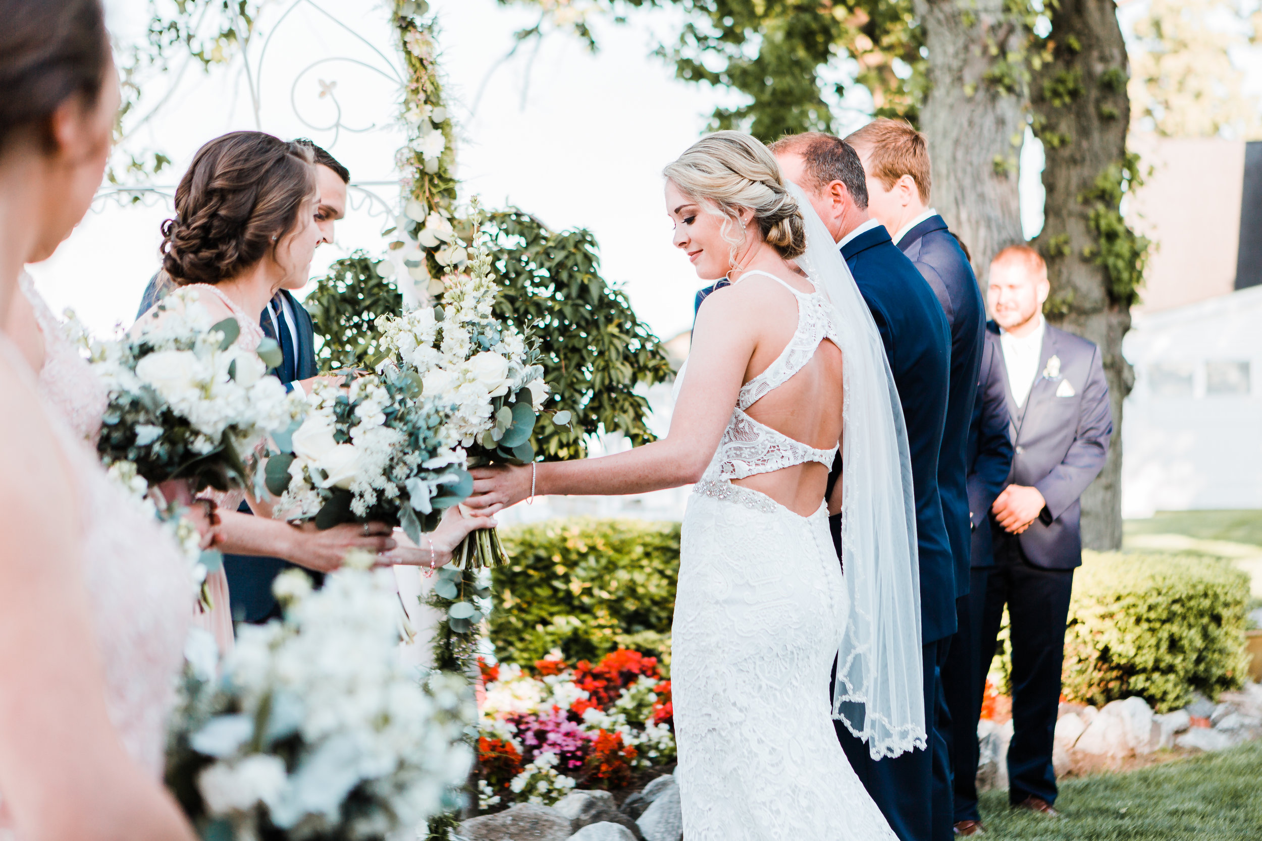 bride handing her bouquet off to her twin sister at celebrations at the bay wedding ceremony