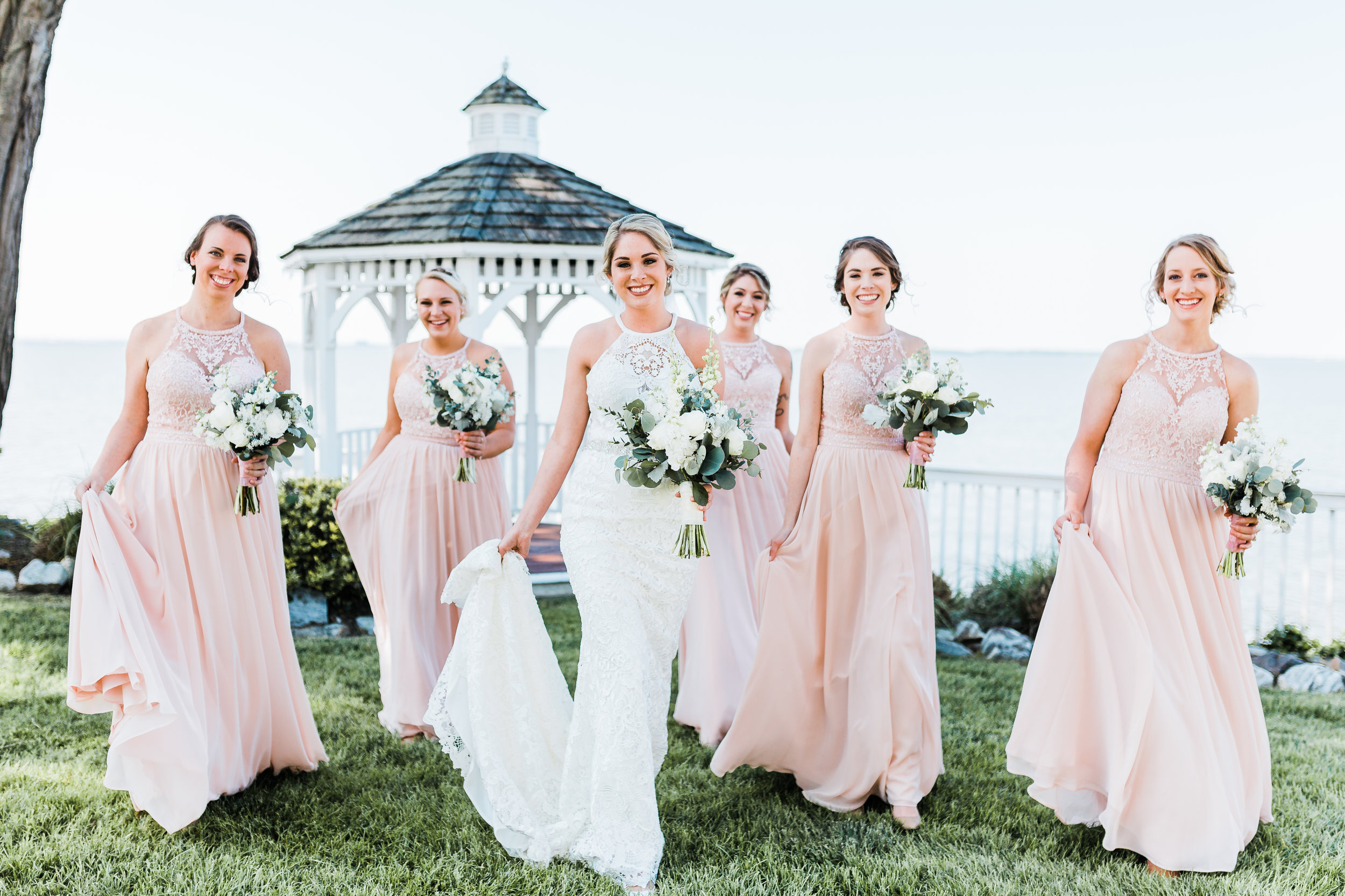 bride walking and laughing with her bridesmaids in modern lace high neck dresses - maryland wedding photographer - bayside wedding