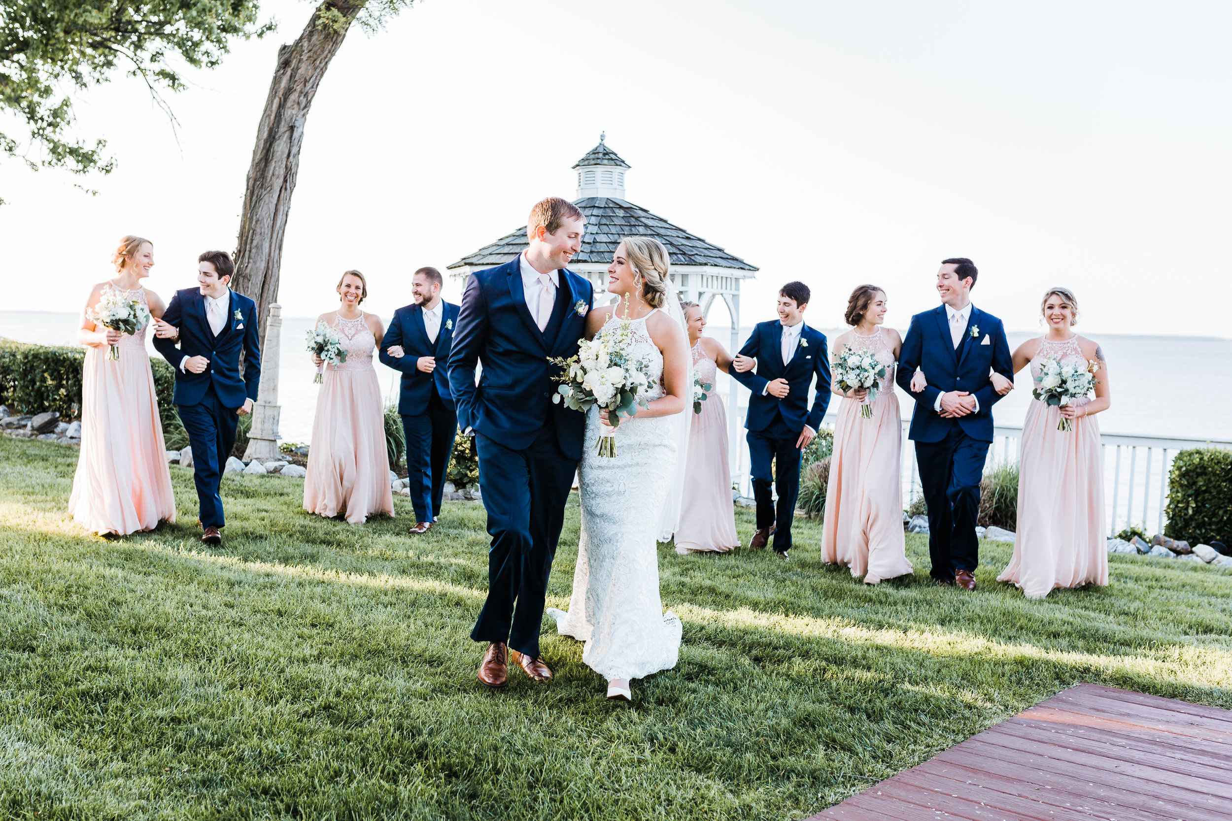 bride and groom smiling at each other with bridal party behind them maryland wedding photographer