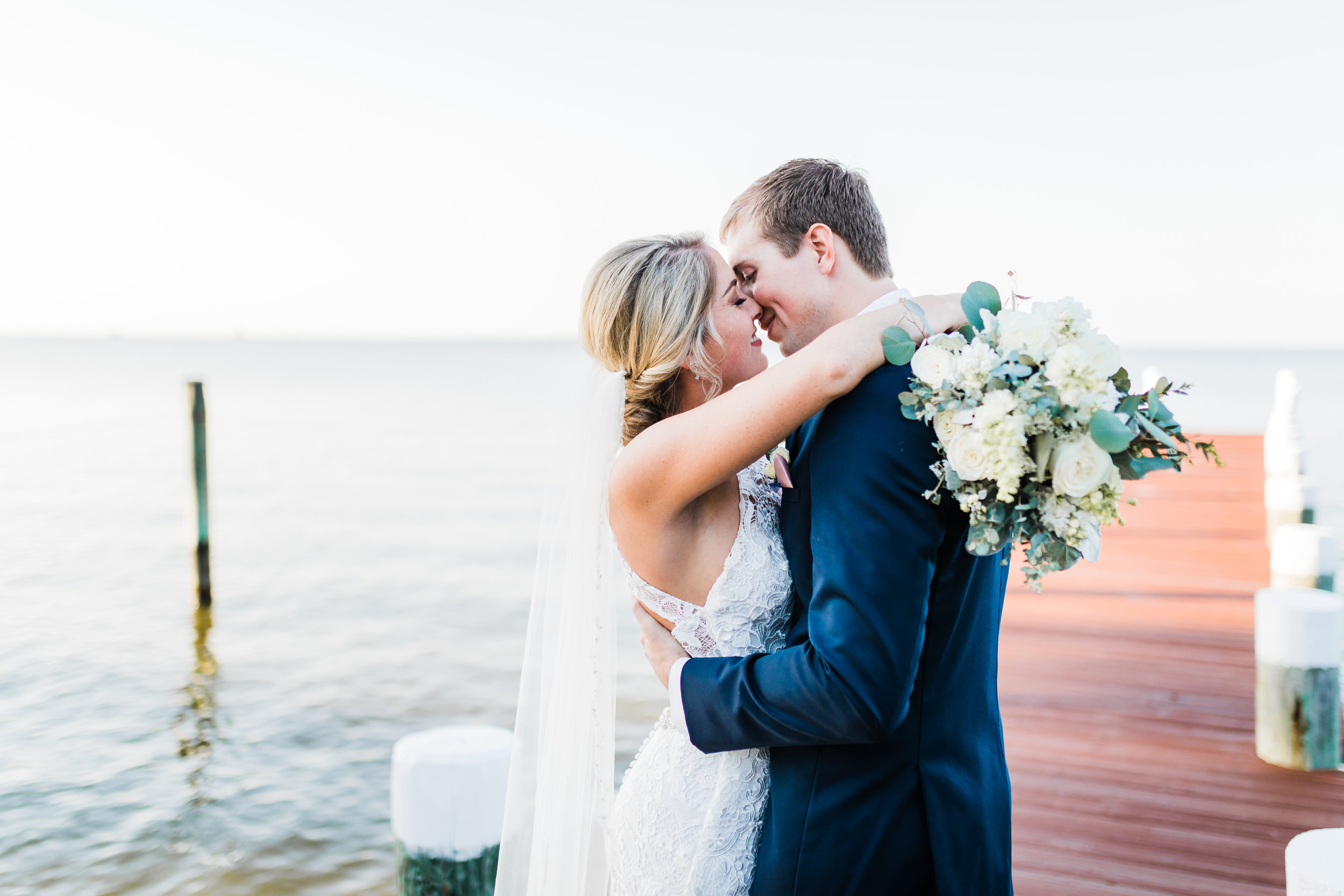 bride kissing her groom on dock at celebrations at the bay - md wedding photographer and videographer